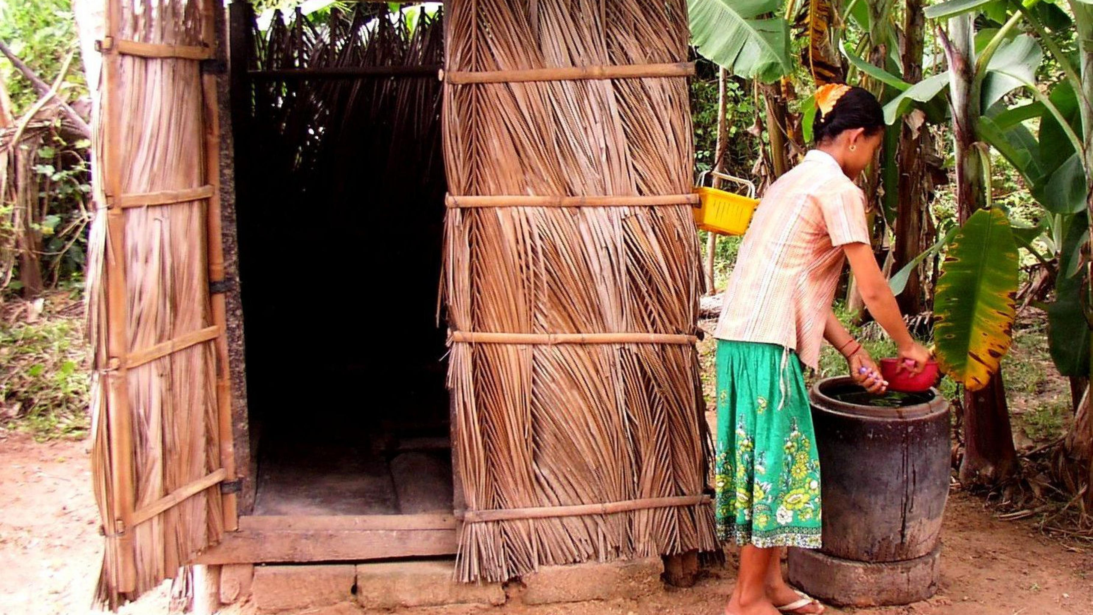 Eine Frau wäscht sich vor einer Toilette die Hände