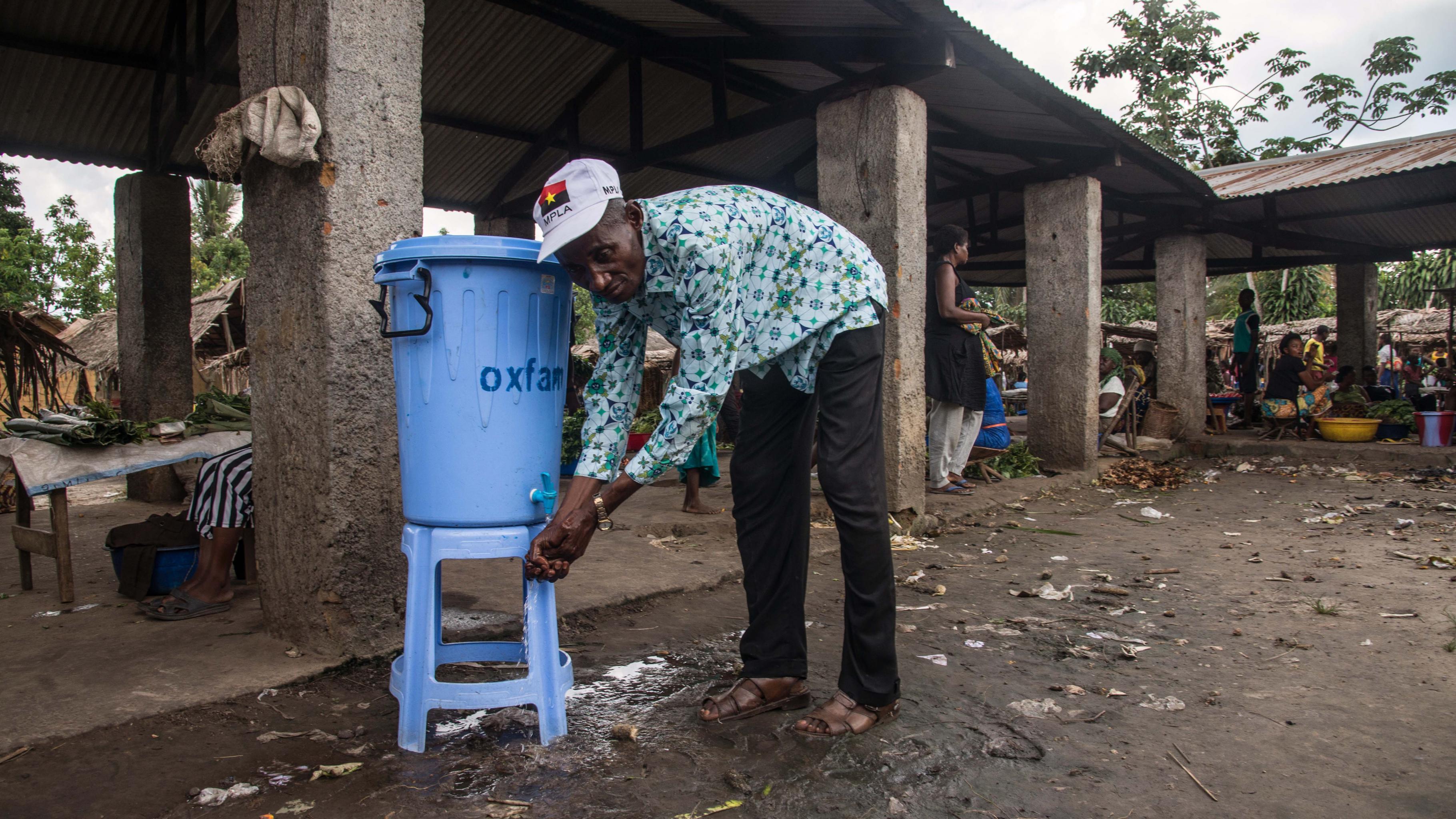 Ein Mann wäscht sich die Hände an einer Oxfam-Wasserstelle.