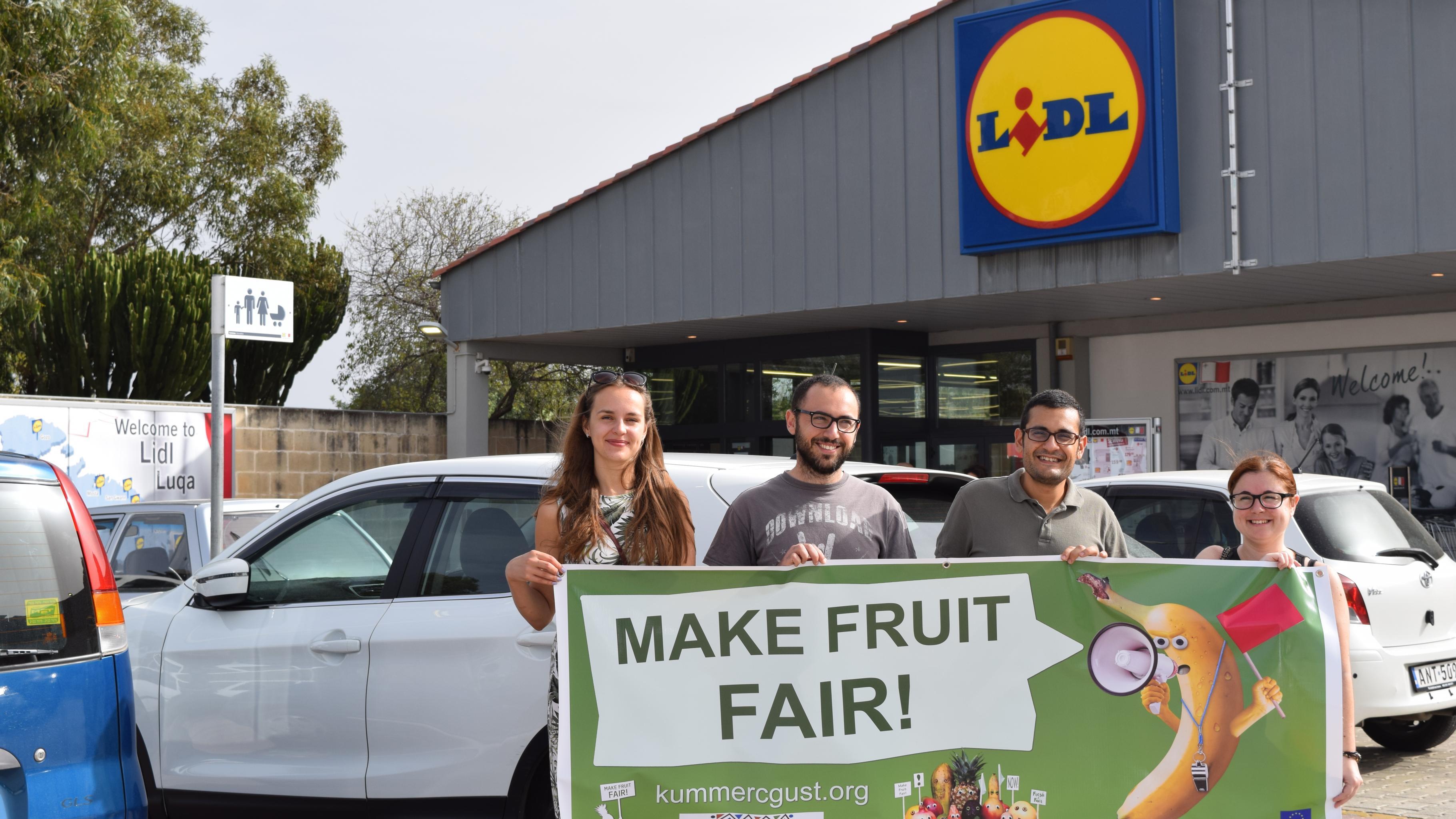 """Aktivist/innen mit einem Transparent vor einer Lidl-Filiale. Auf dem Transparent fordert eine wütende Banane per Megafon: """"Make Fruit Fair!"""""""