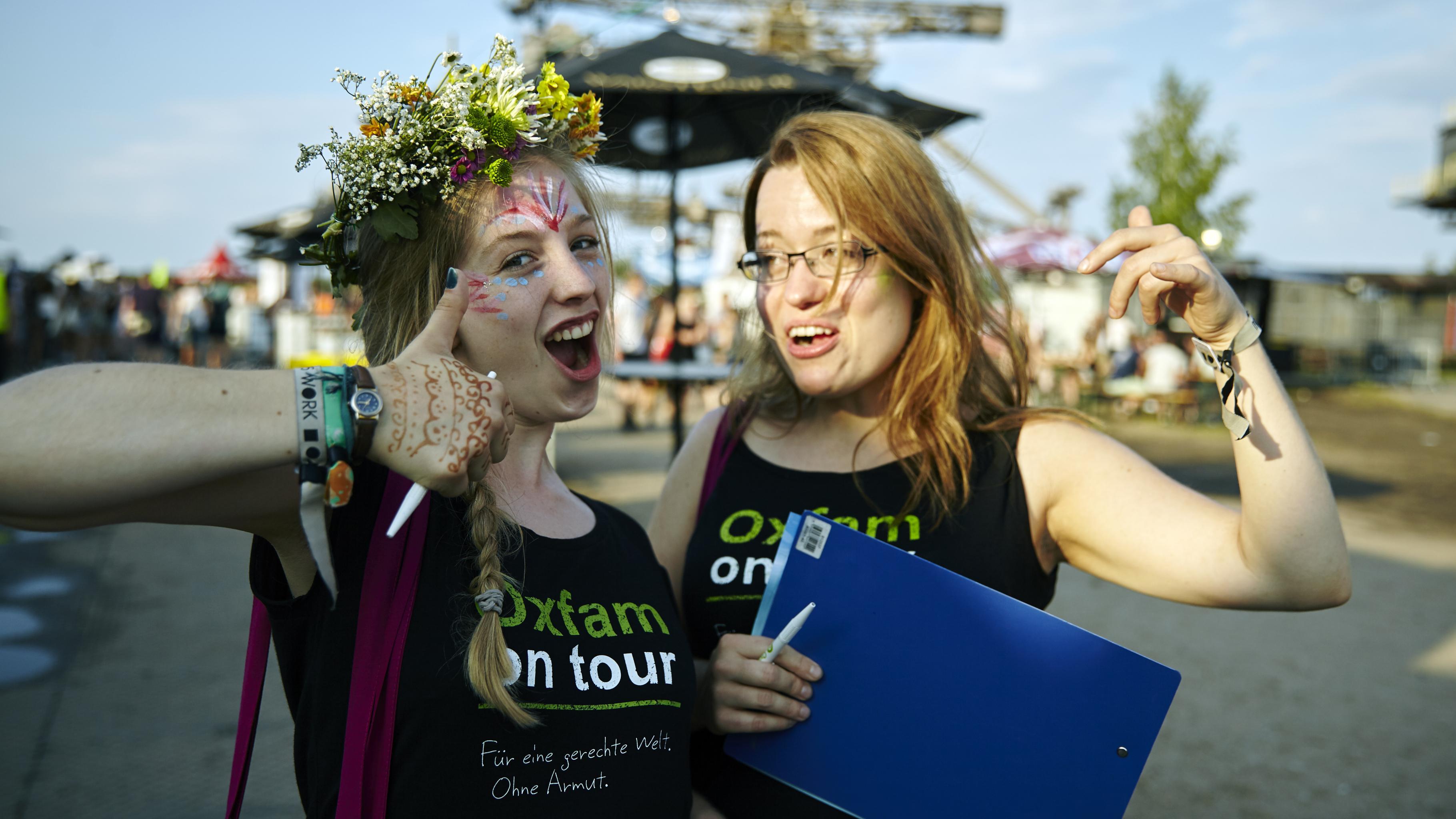 Zwei Konzertaktivistinnen mit einem mit Oxfam on Tour bedrucktem T-Shirt vor dem Hintergrund des Melt-Festivals