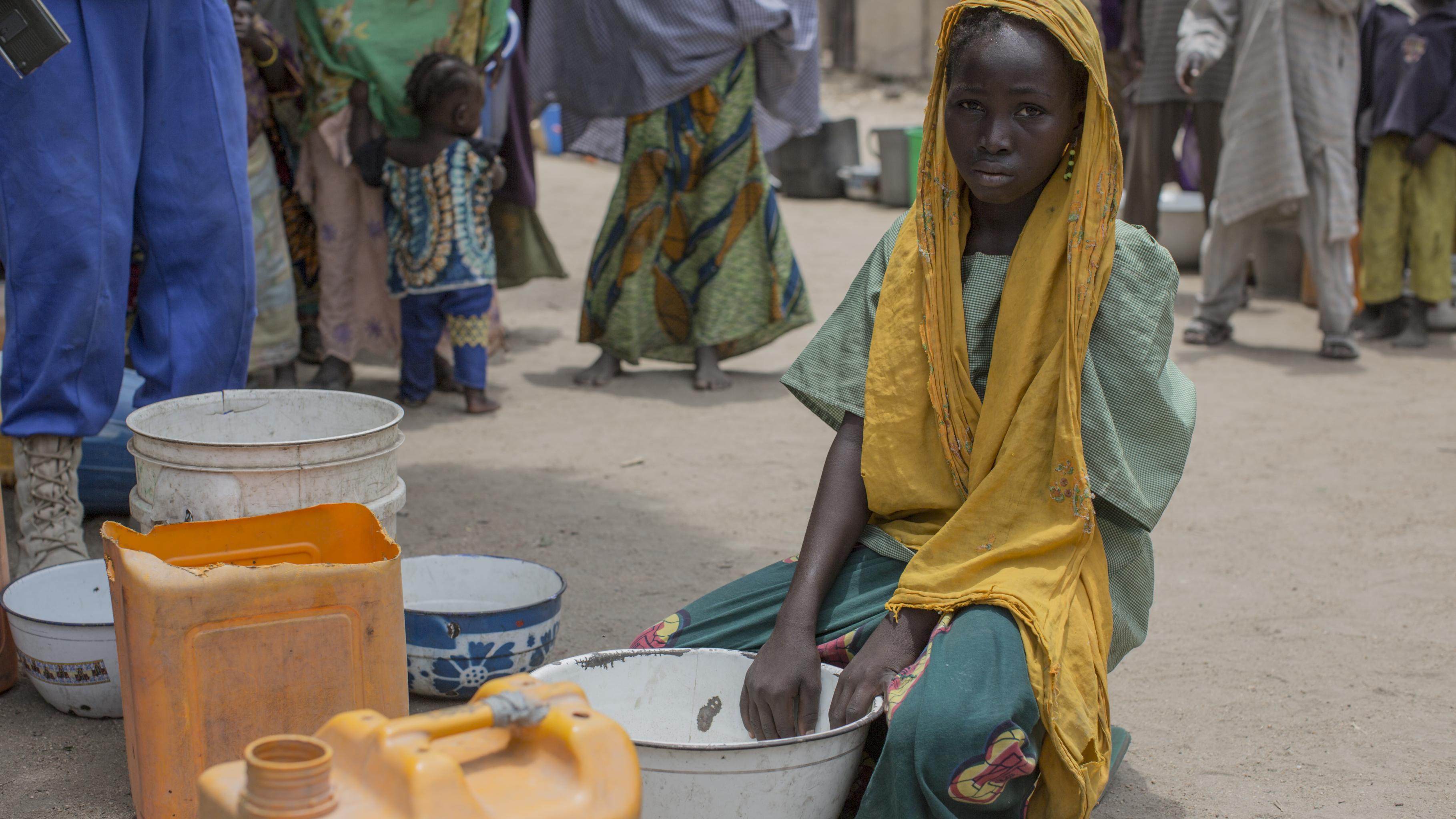 Ein Mädchen sitzt mit Wasserbehältern auf dem Boden.