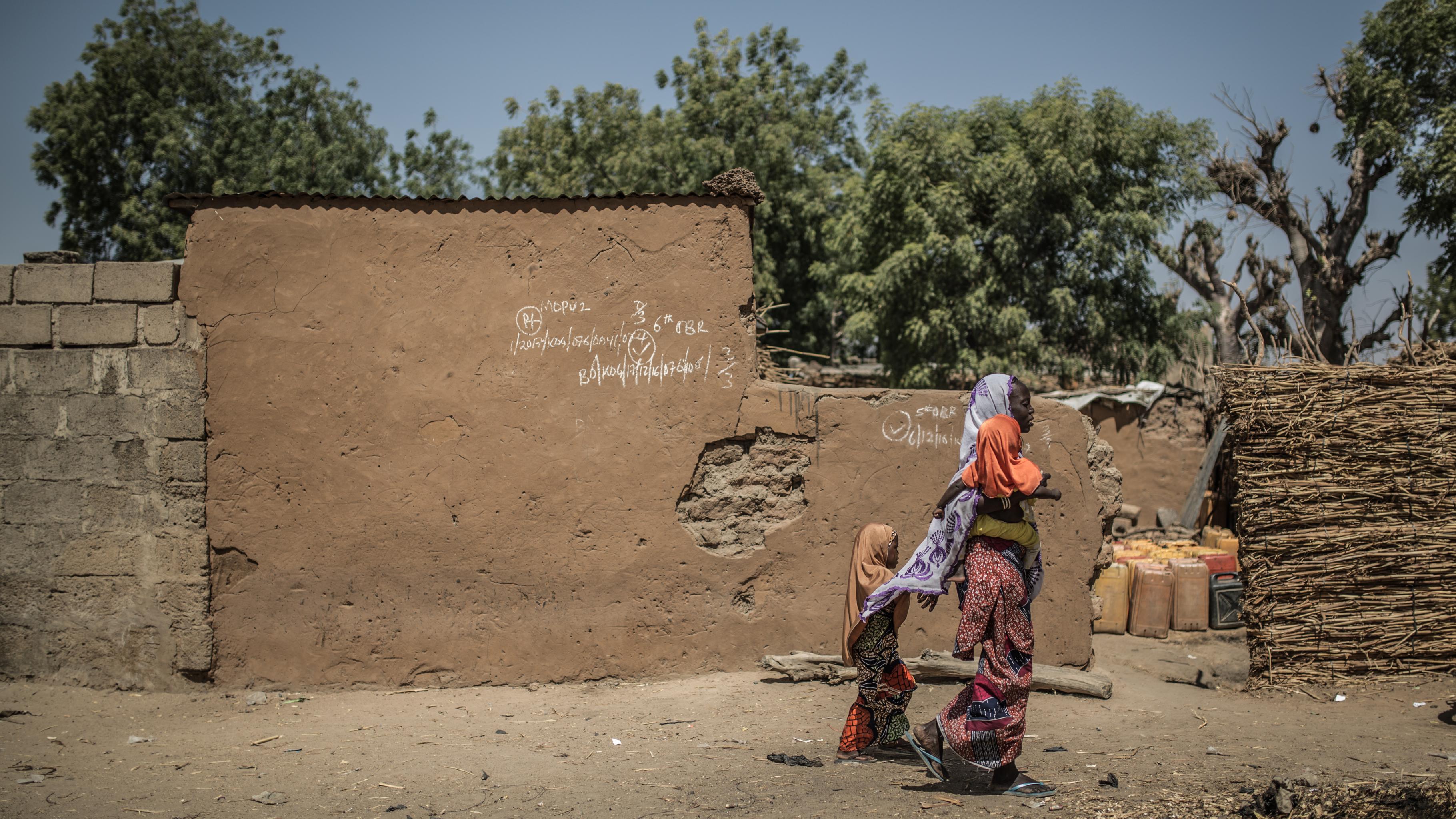 Eine Frau mit einem Kind auf dem Arm und einem zweiten an der Hand geht an einer Hauswand vorbei.