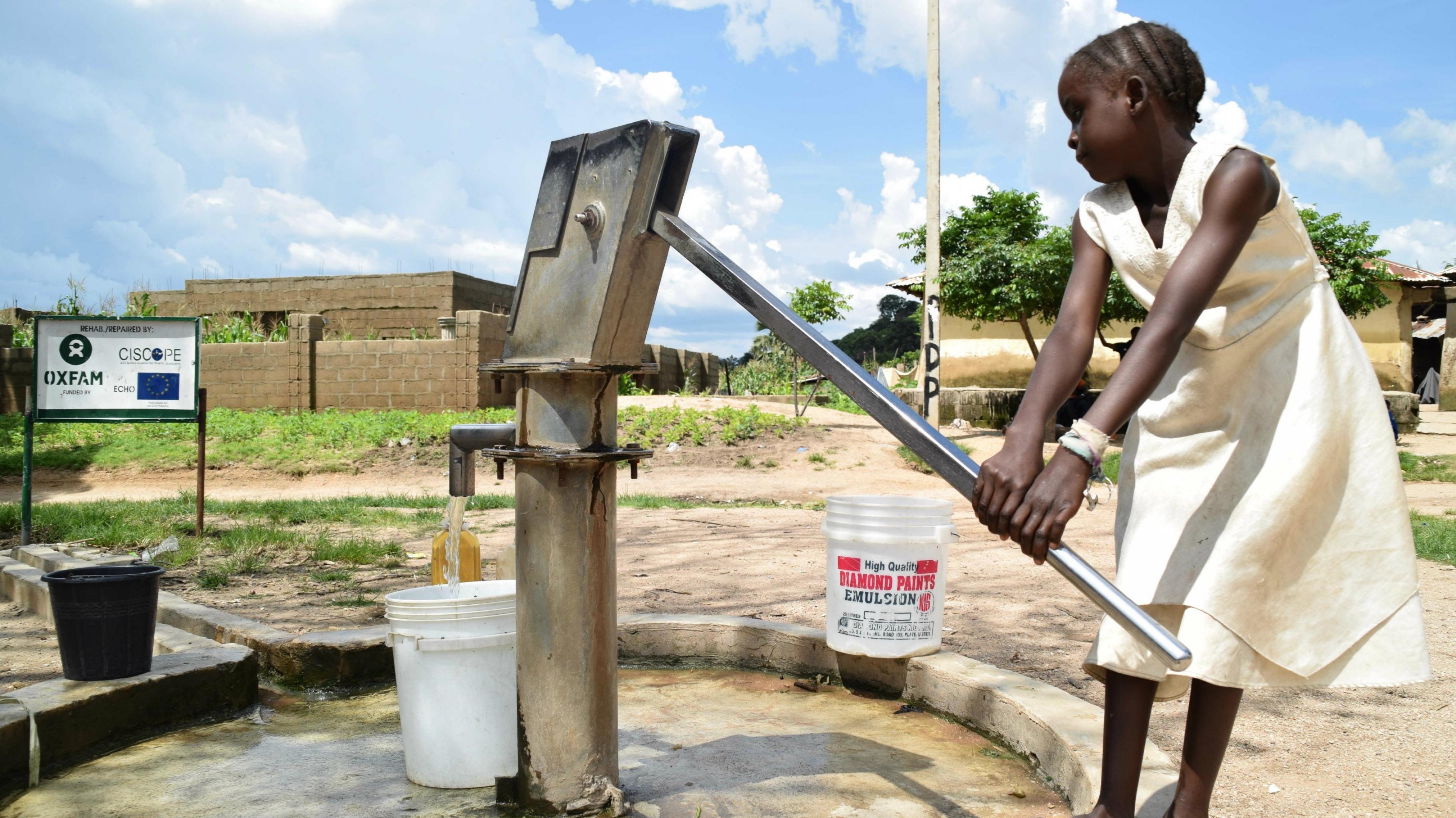 Ein Mädchen betätigt eine Handpumpe, um einen Eimer mit Wasser zu füllen.