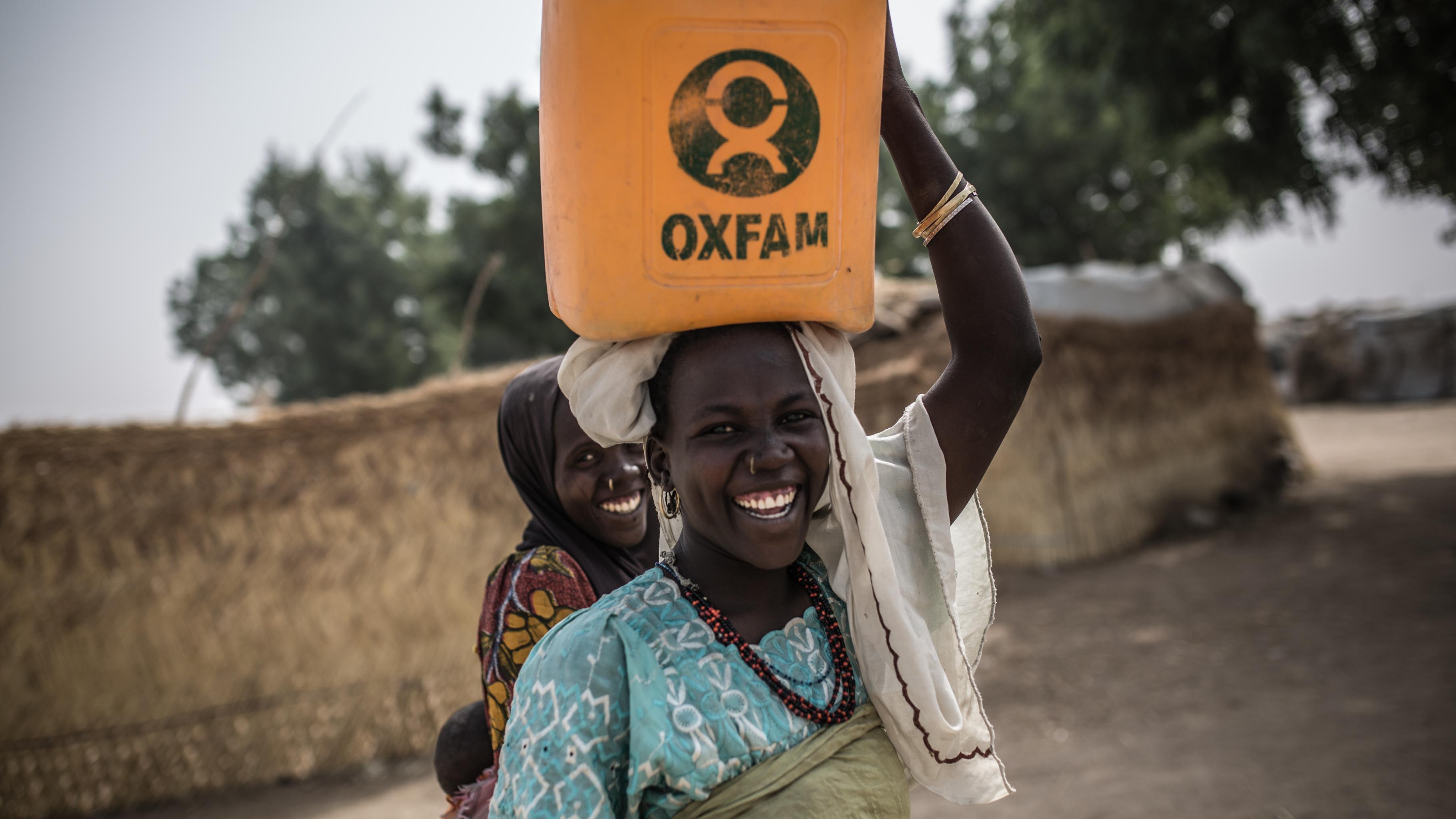 Zwei Frauen lachen; eine von ihnen transportiert einen Oxfam-Wasserkanister auf dem Kopf.