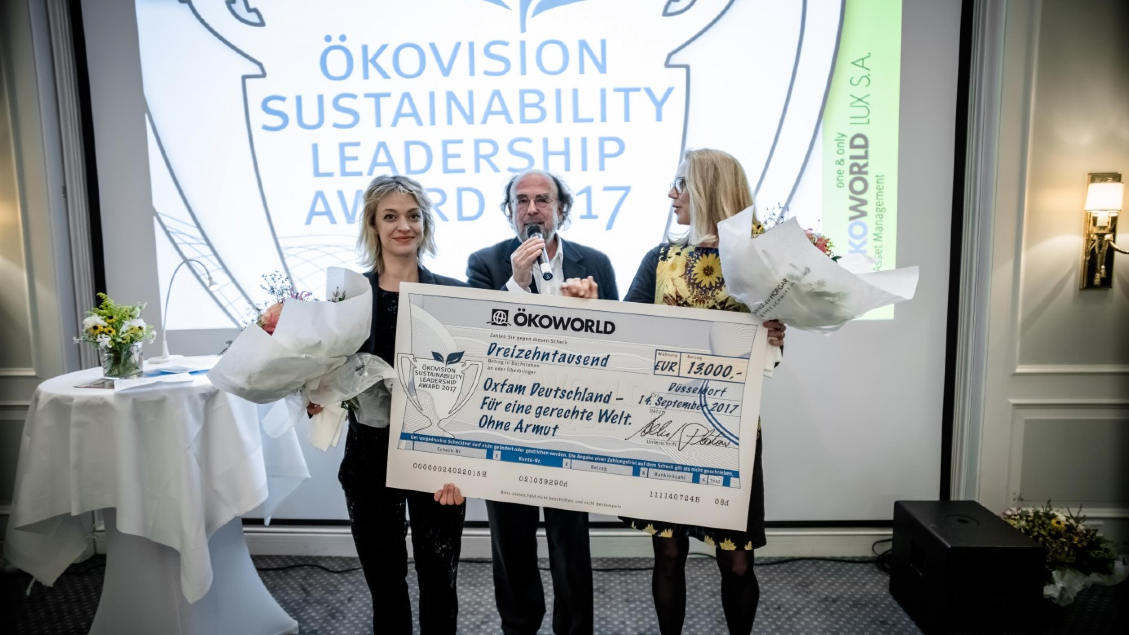Alfred Platow, Gründer und Vorstandsvorsitzender von Ökoworld, übergibt Oxfam-Botschafterin Heike Makatsch und Geschäftsführerin Marion Lieser einen Scheck im Wert von 13.000 Euro.