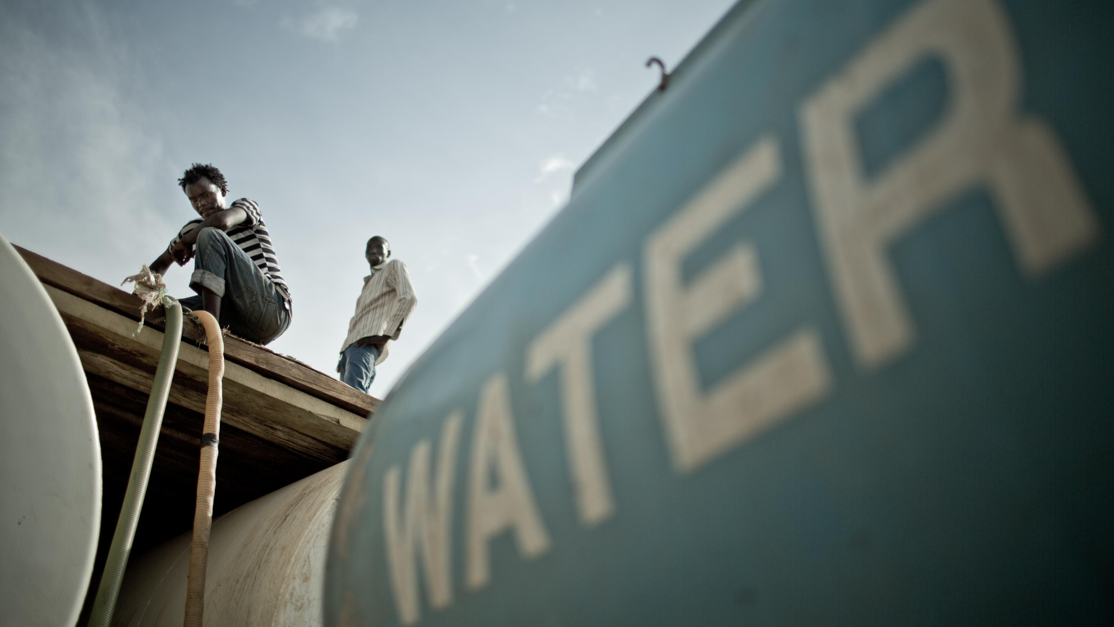 Wasser wird aus einem Wasserwagen gepumpt.