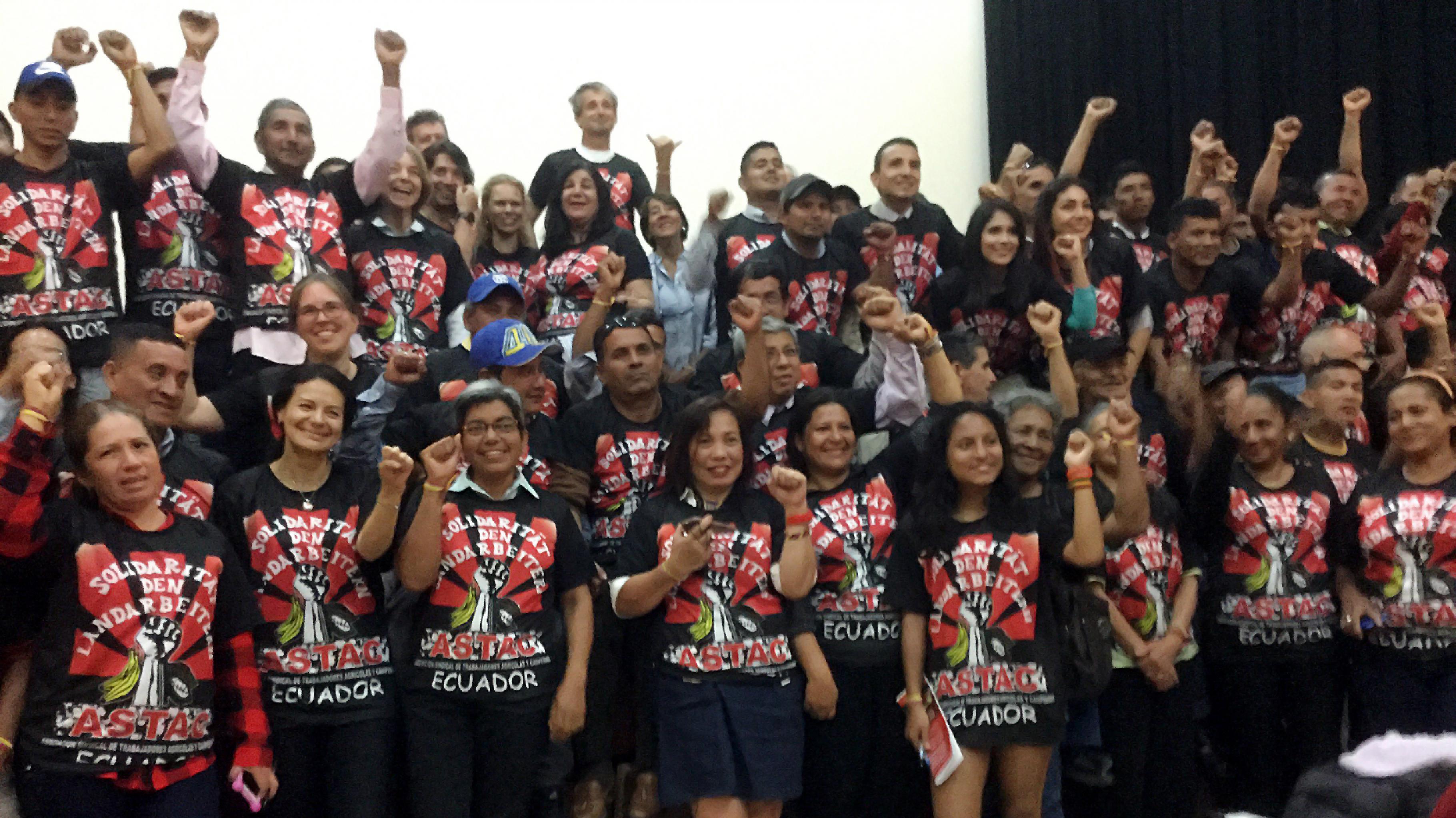 """Gruppenfoto; alle tragen ein T-Shirt mit der Aufschrift """"Solidarität mit den Landarbeitern – ASTAC – Ecuador"""" und heben die Fäuste"""