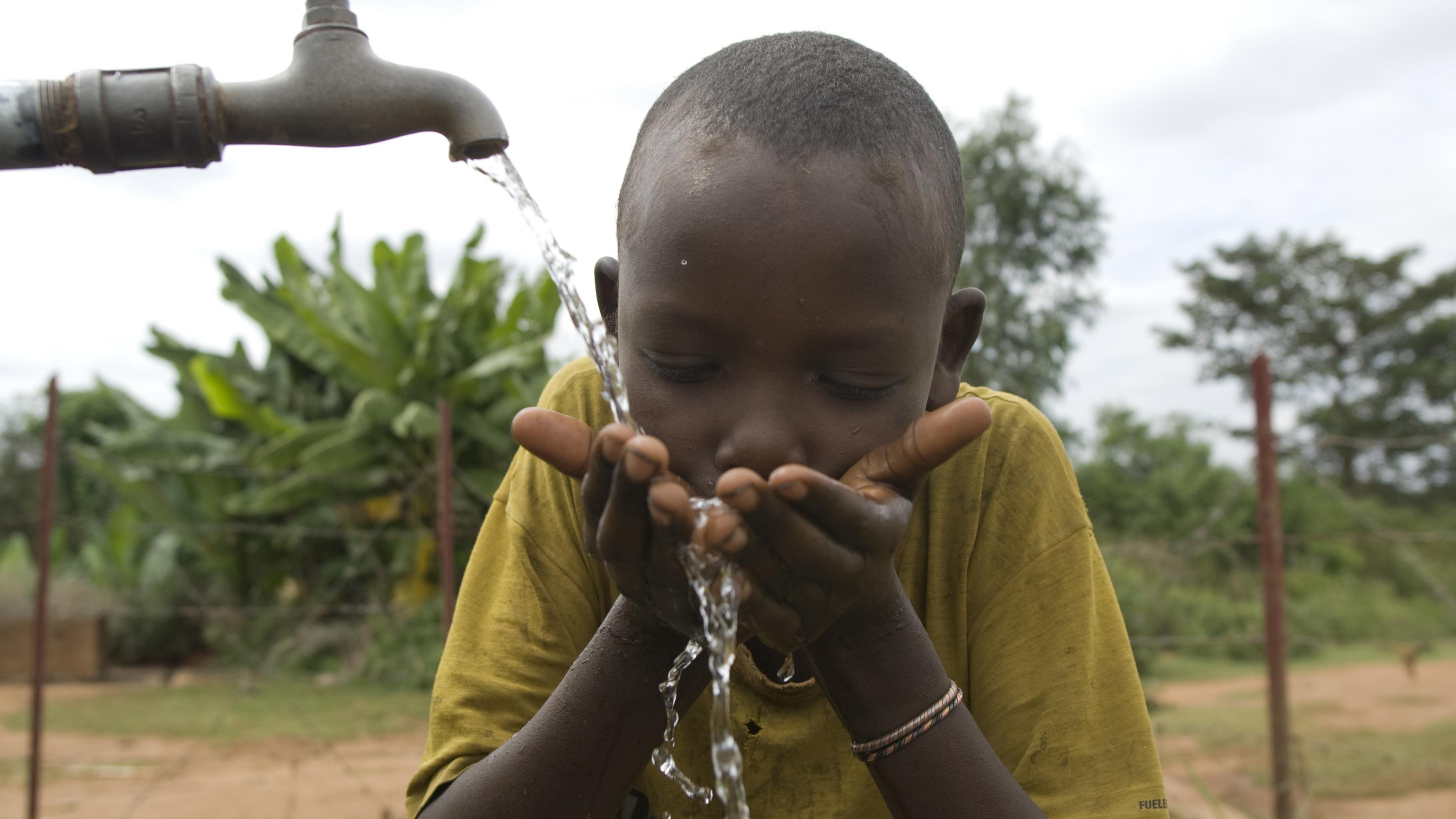 Äthiopien, Junge trinkt Wasser aus Hahn