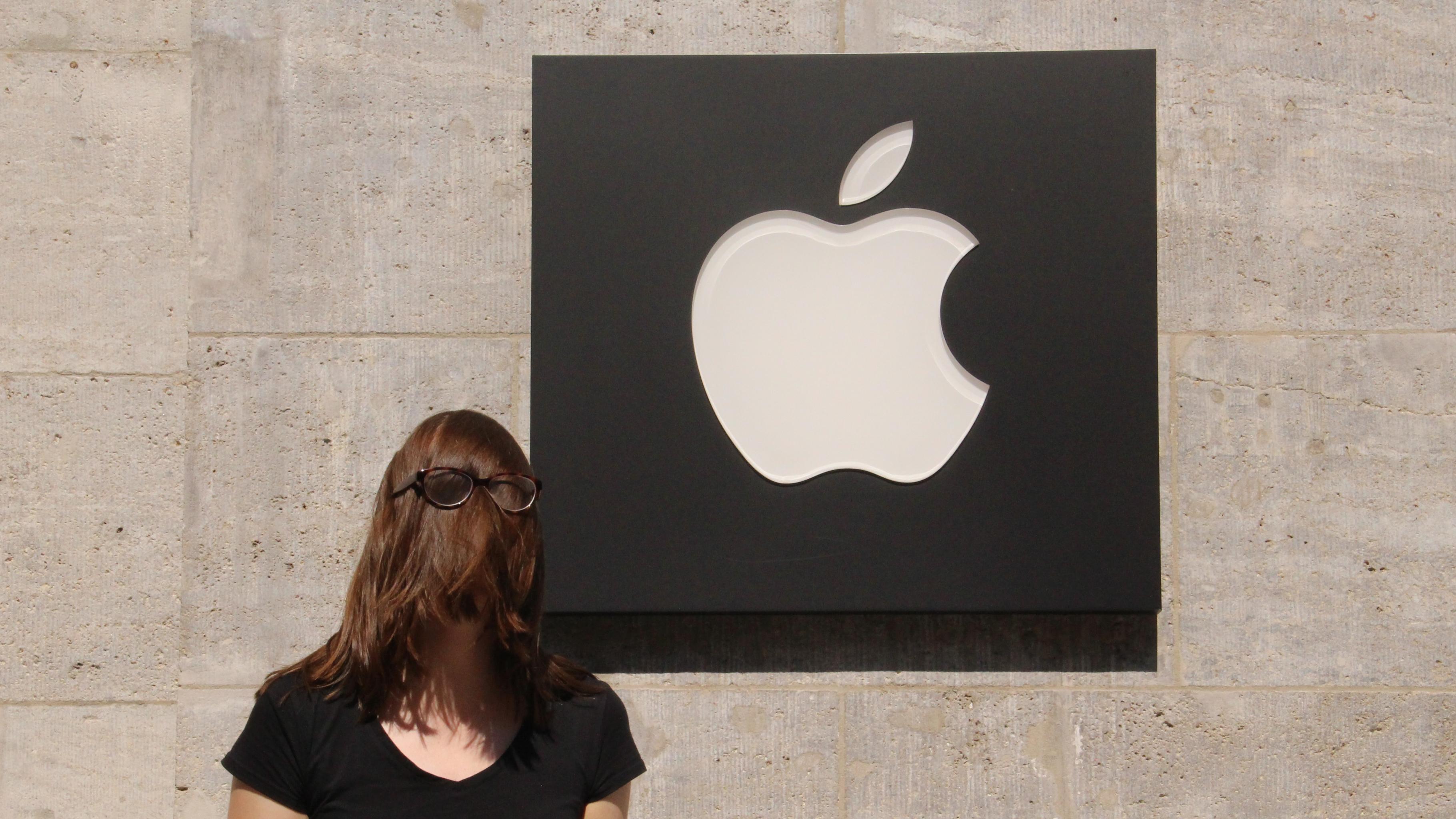 Eine Aktivistin vor einem Apple-Logo, ihr Gesicht ist durch Haare und einer darüber gezogenen Brille verdeckt