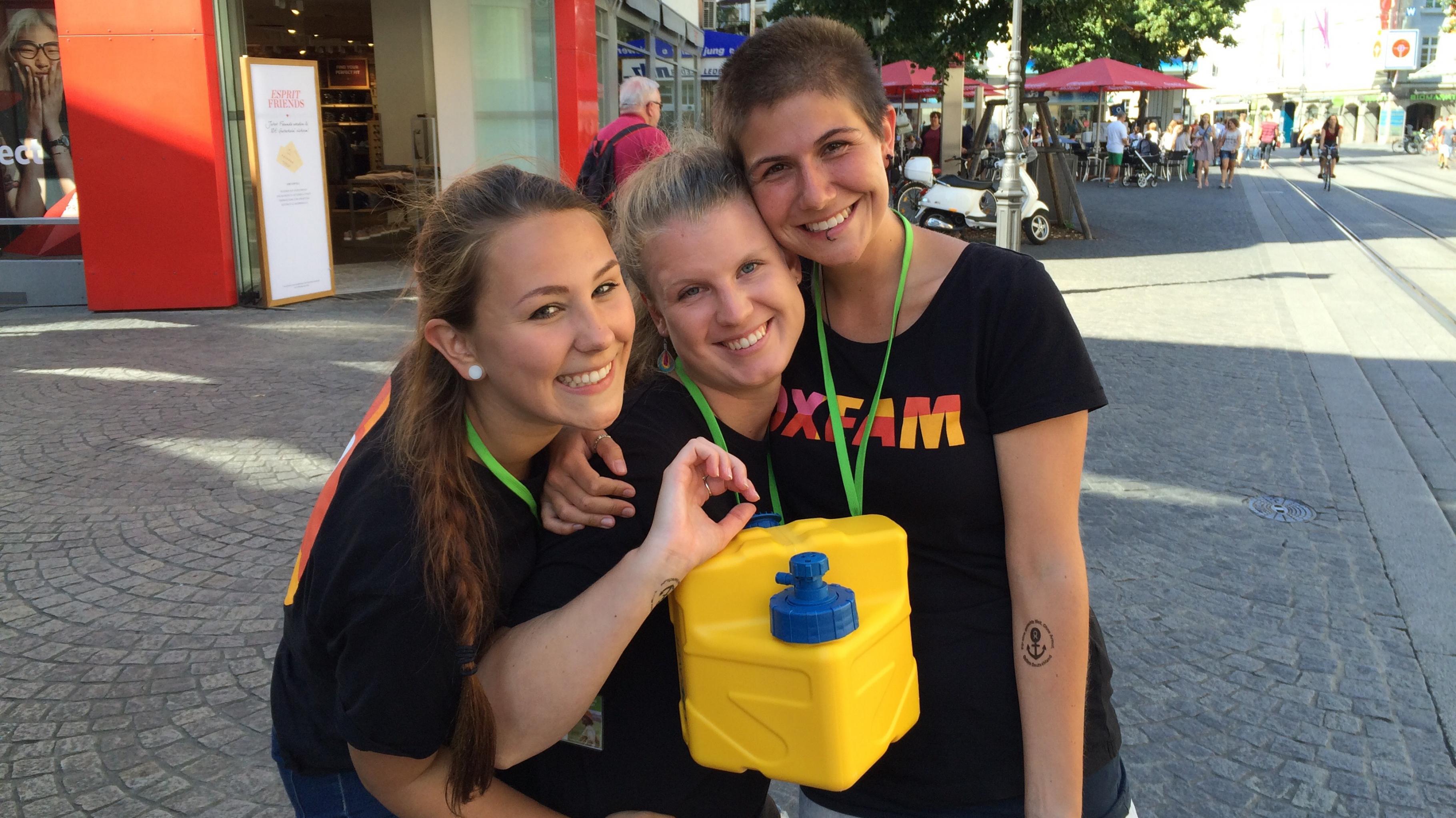 Drei Oxfam-Mitarbeiterinnen in einer Fußgängerzone