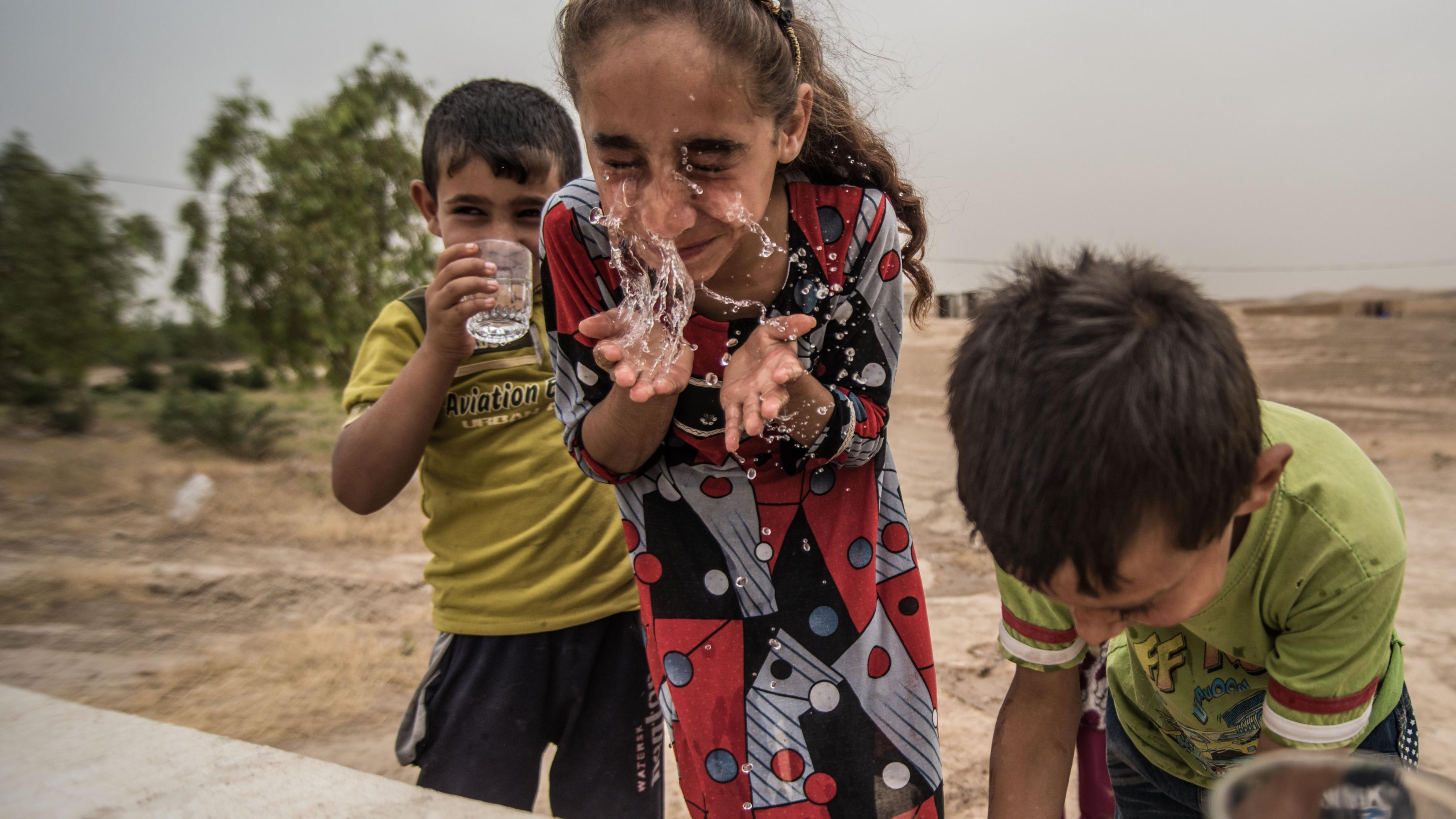 Drei Kinder trinken und waschen sich an einem Wasserhahn.