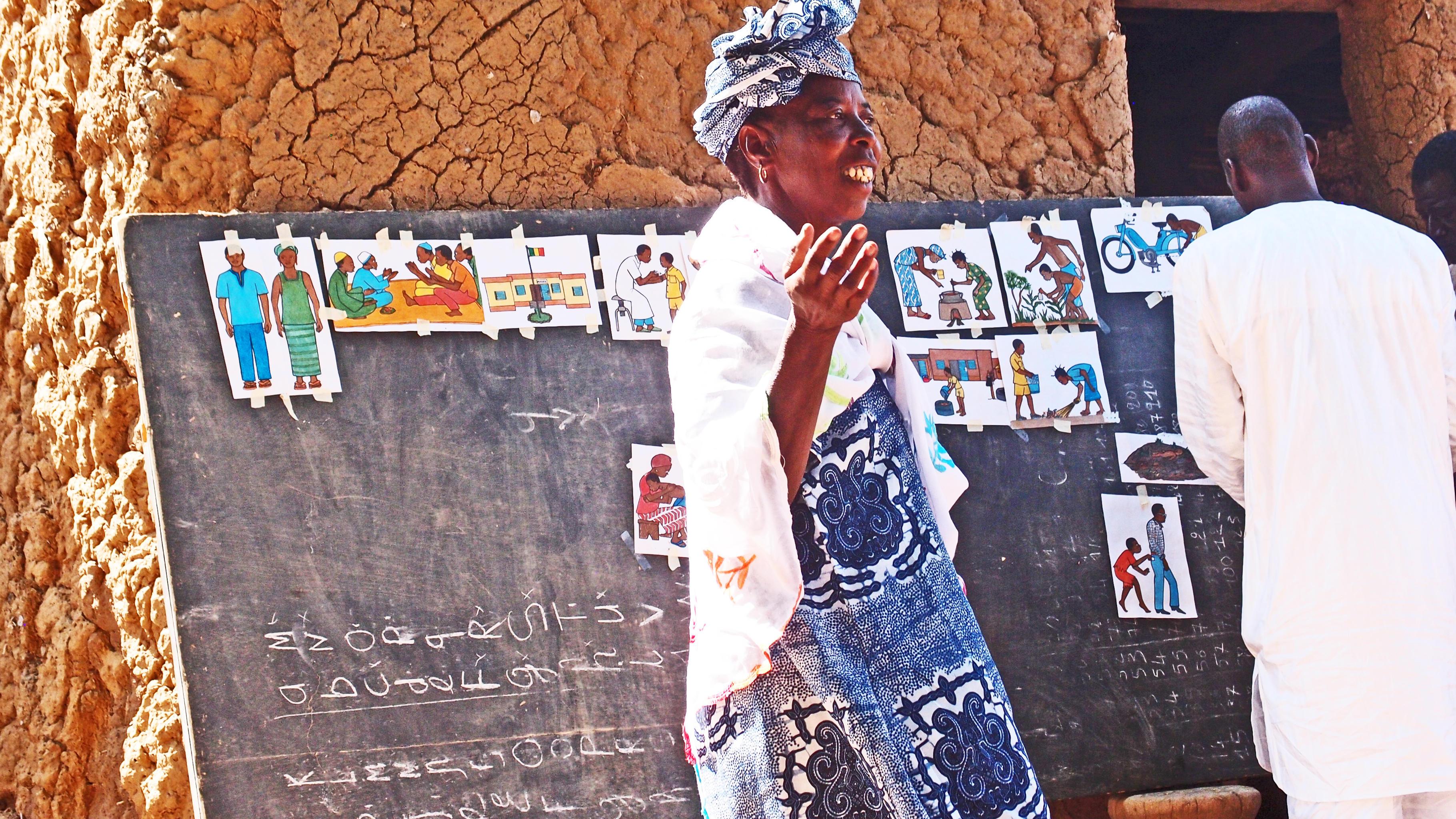 Frau vor Tafel mit Bildern zur Aufklärung gegen FGM
