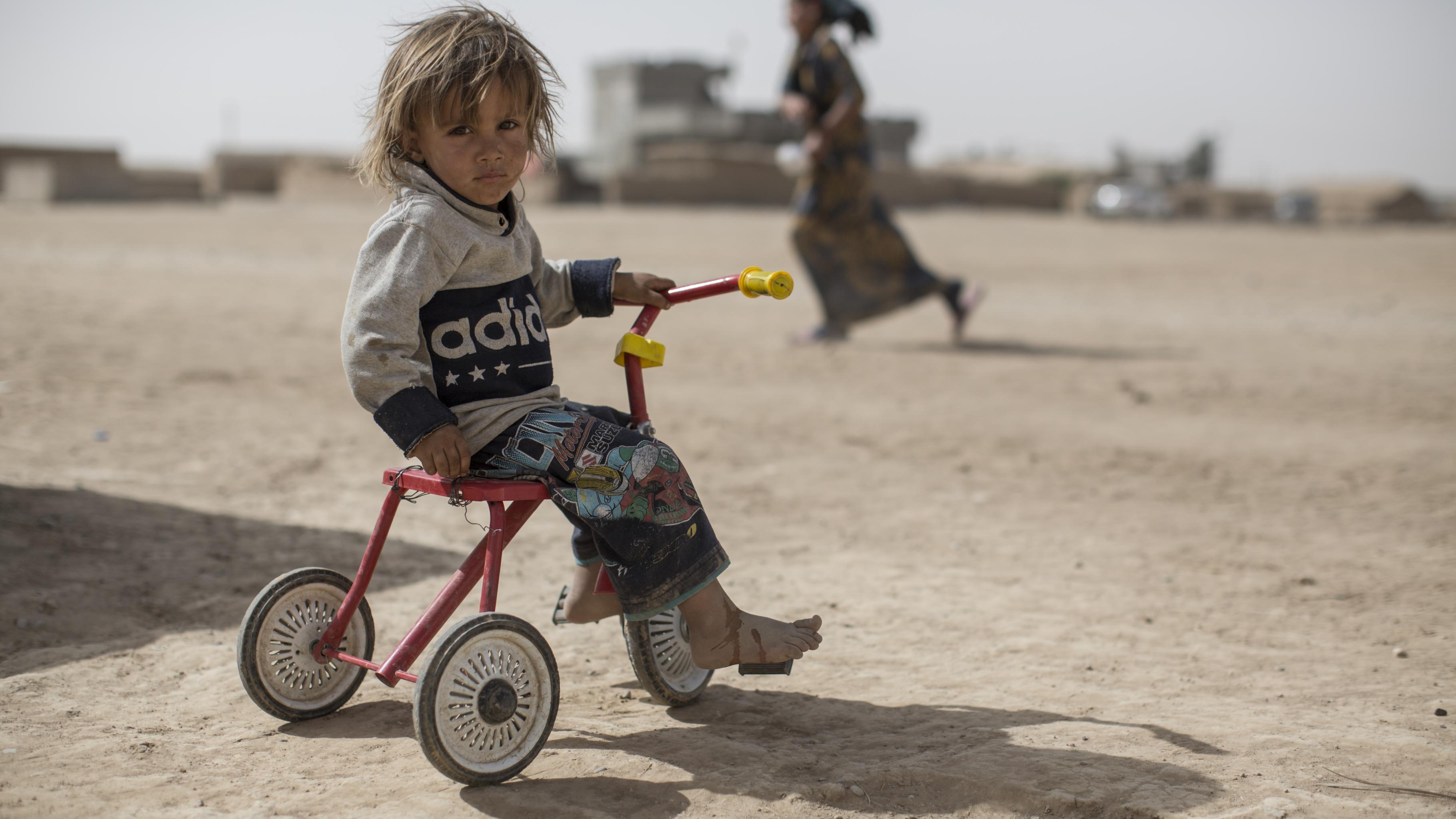 Kind auf einem Dreirad in einem Flüchtlingscamp in Tinah bei Mossul.