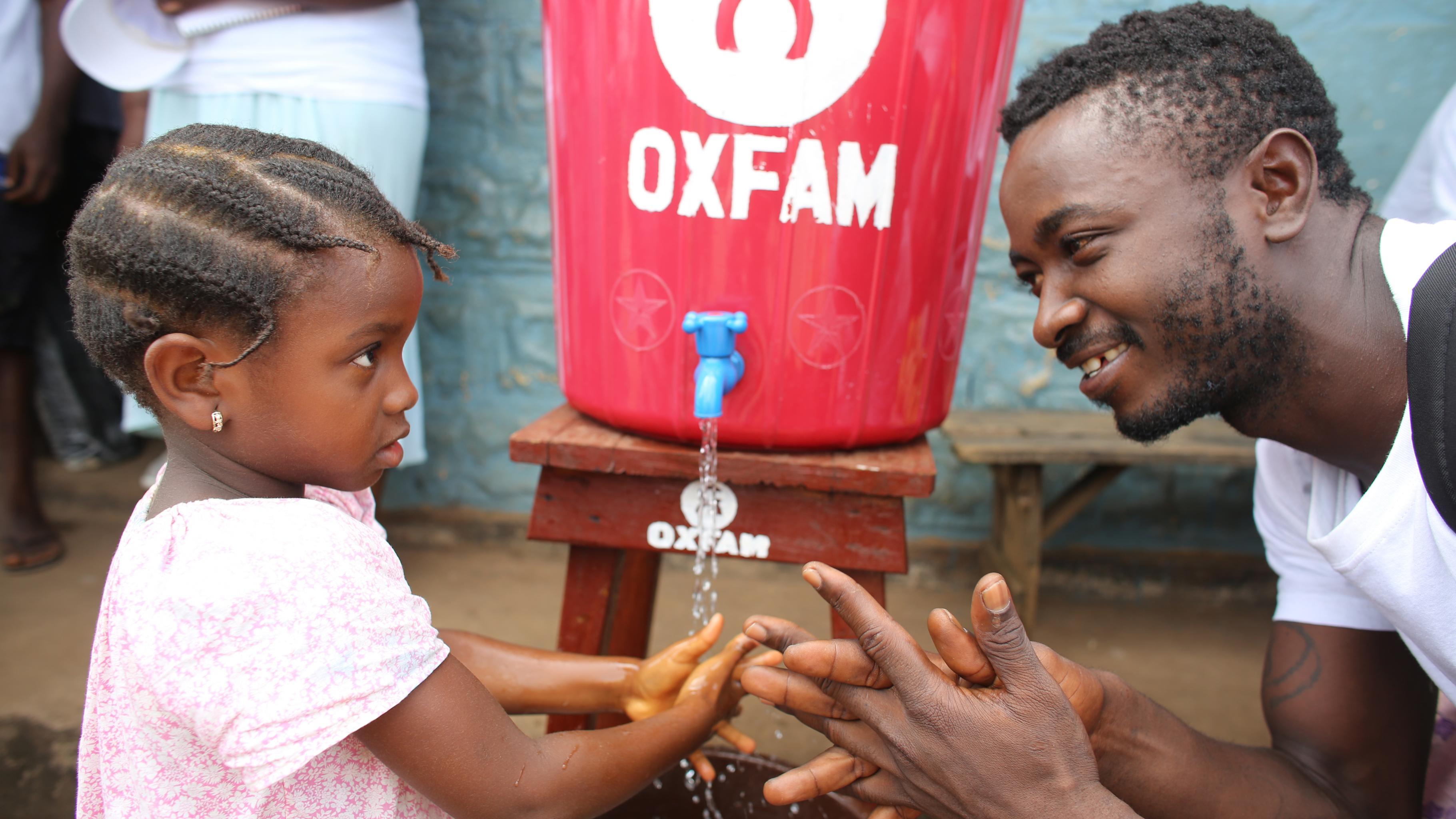 Mann zeigt Kind wie es Hände waschen soll