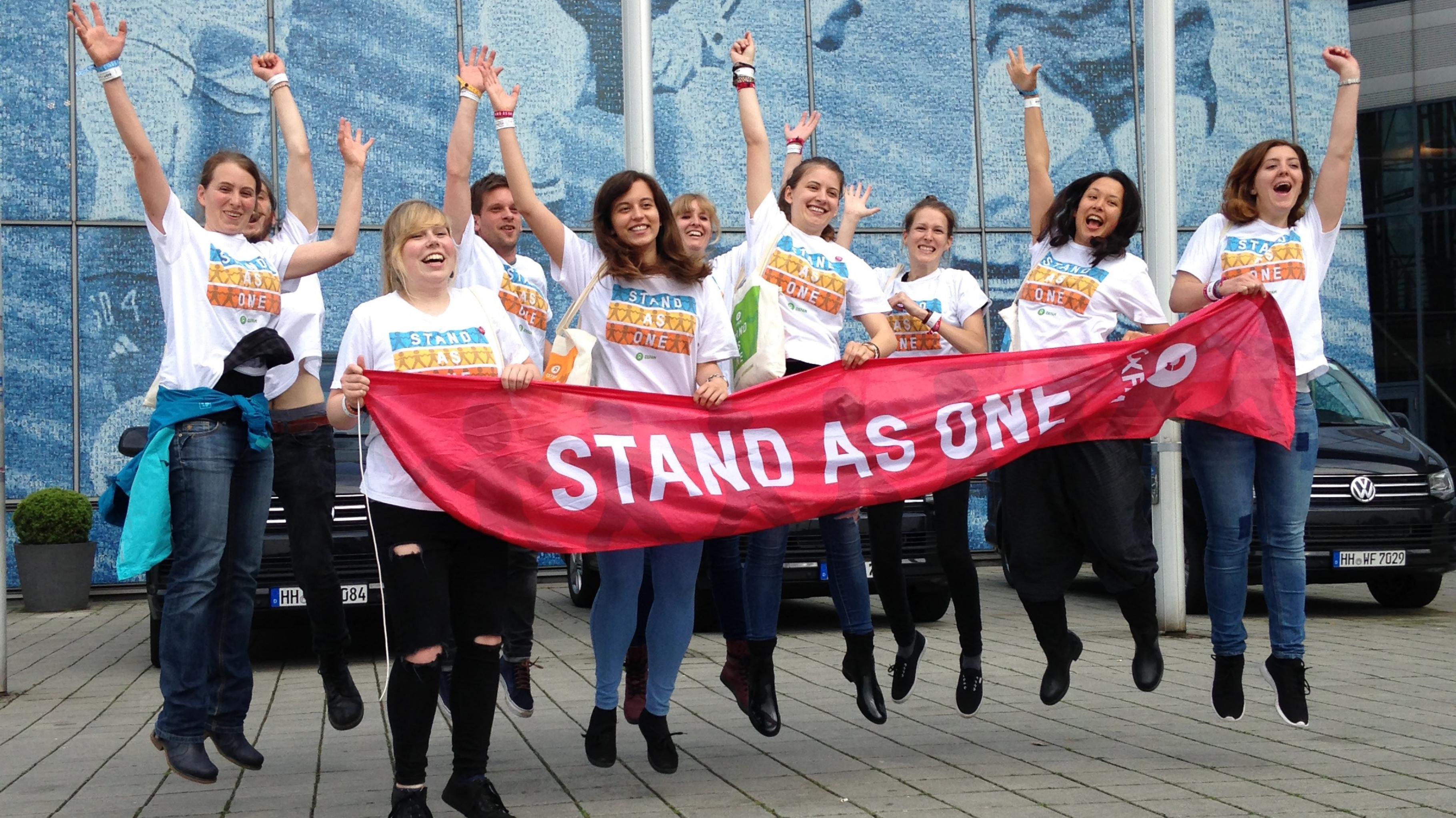 Hüpfende Konzertaktivistinnen halten ein Banner mit der Aufschrift: Stand As One