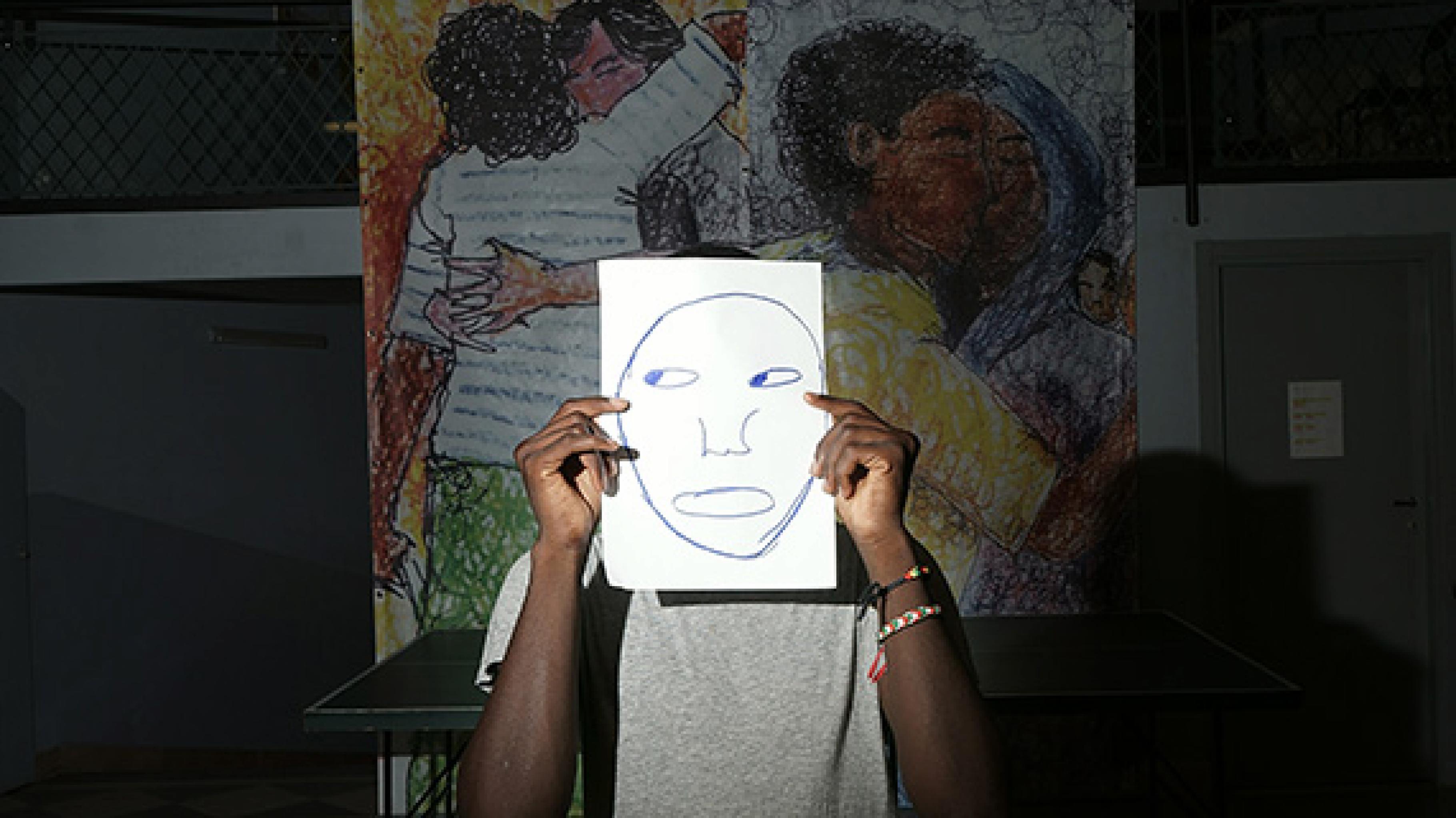 Ein Jugendlicher verdeckt sein Gesicht durch ein weißes Papier, auf dem ein Gesicht aufgemalt ist