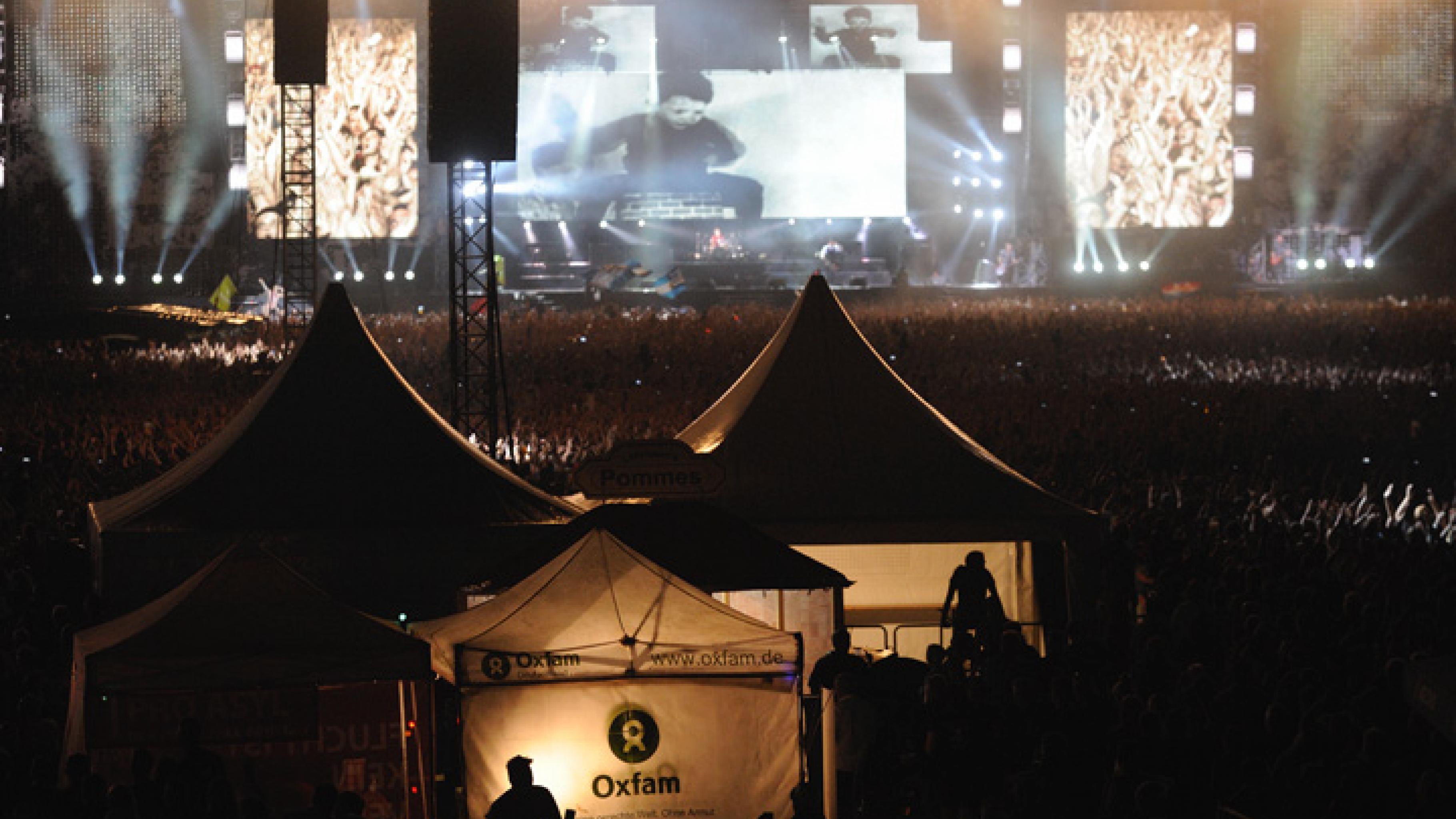 Ein hell beleuchtetes Oxfam-Zelt vor großer Bühne