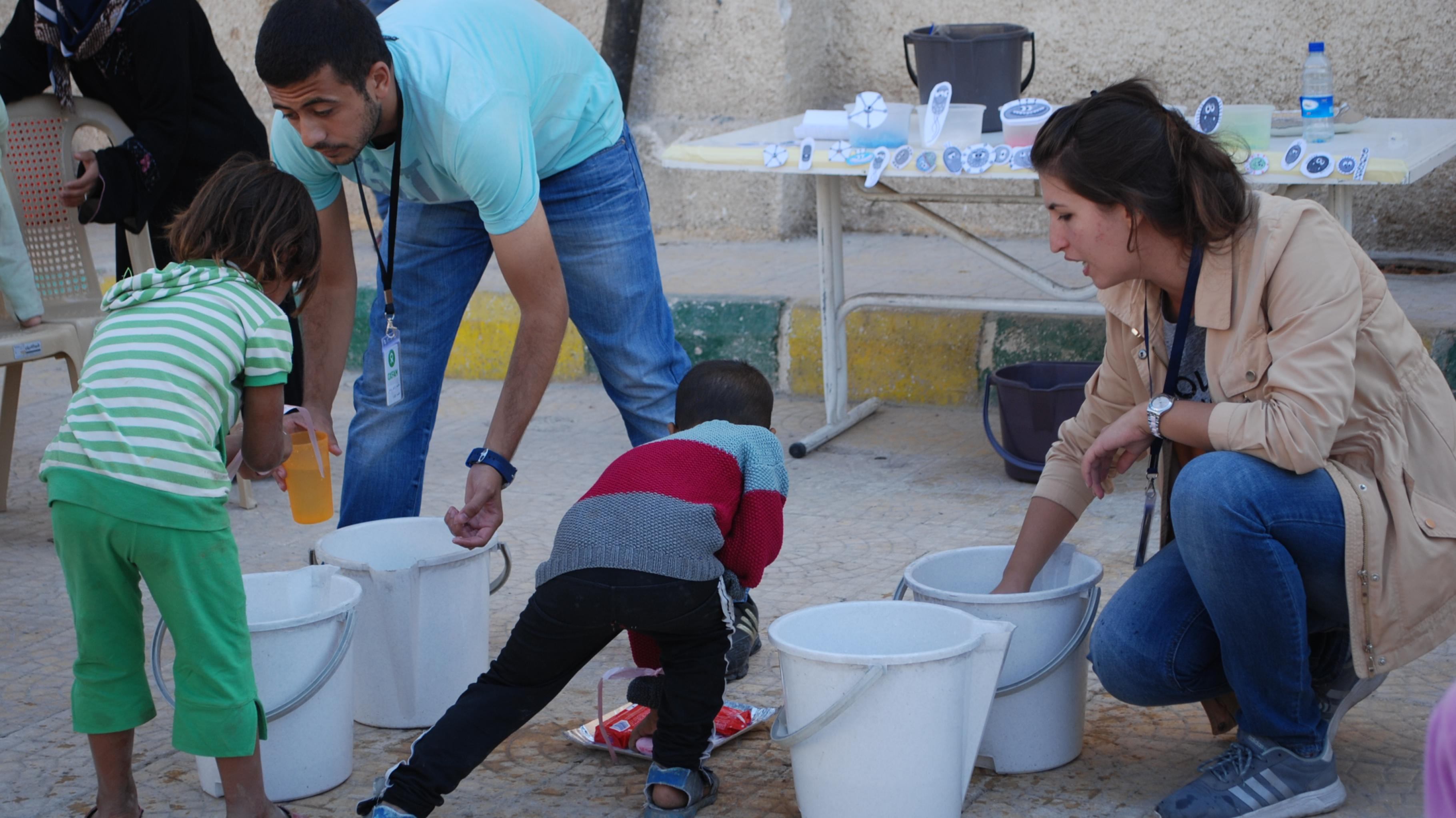 Eine Oxfam-Mitarbeiterin und ein Oxfam-Mitarbeiter erklären Kindern spielerisch die Bedeutung des Hände waschens.