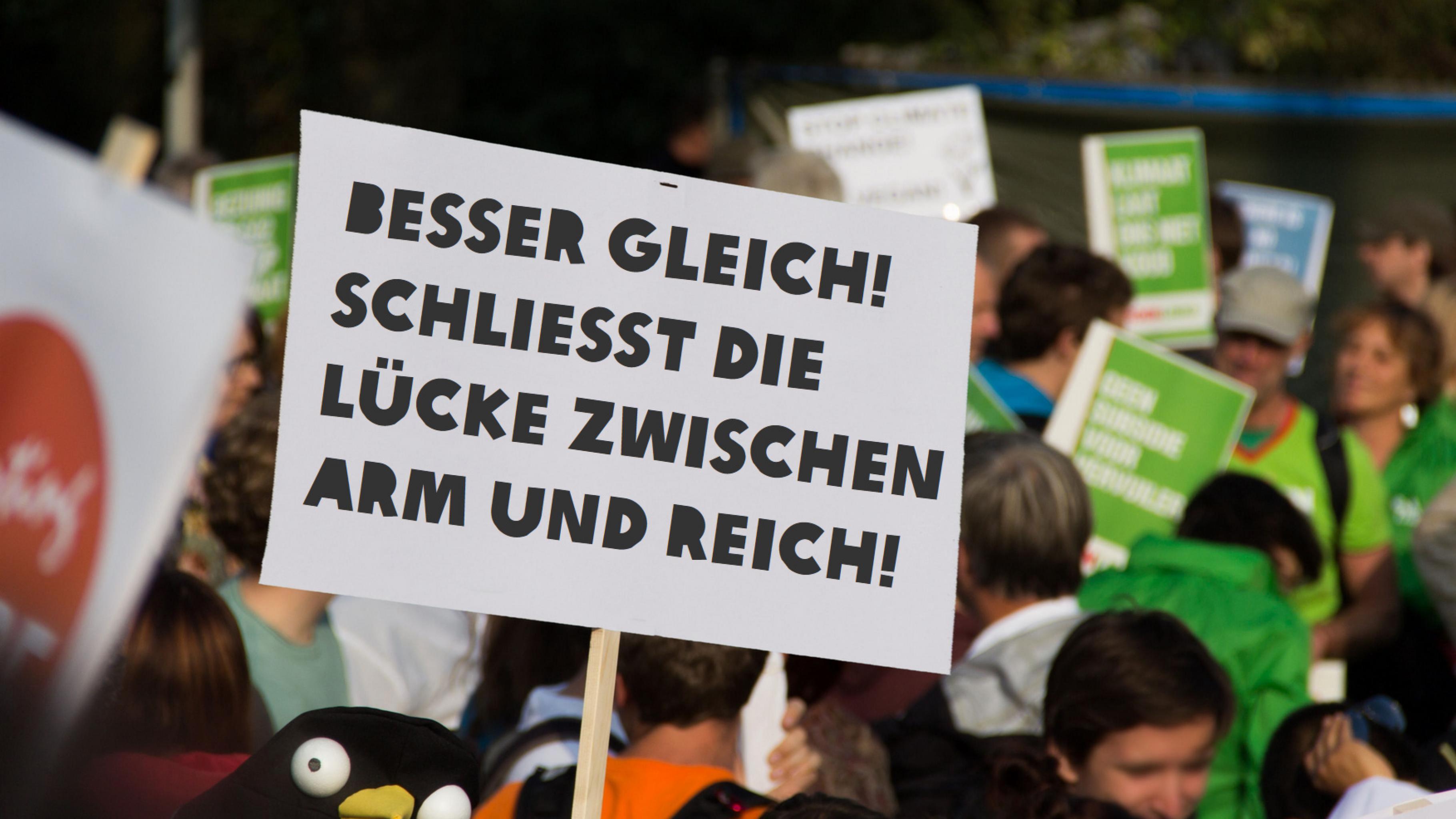 """Im Vordergrund ein Schild mit der Aufschrift: """"Besser Gleich! Schließt die Lücke zwischen Arm und Reich!"""" Im Hintergrund Menschen auf einer Demonstration"""