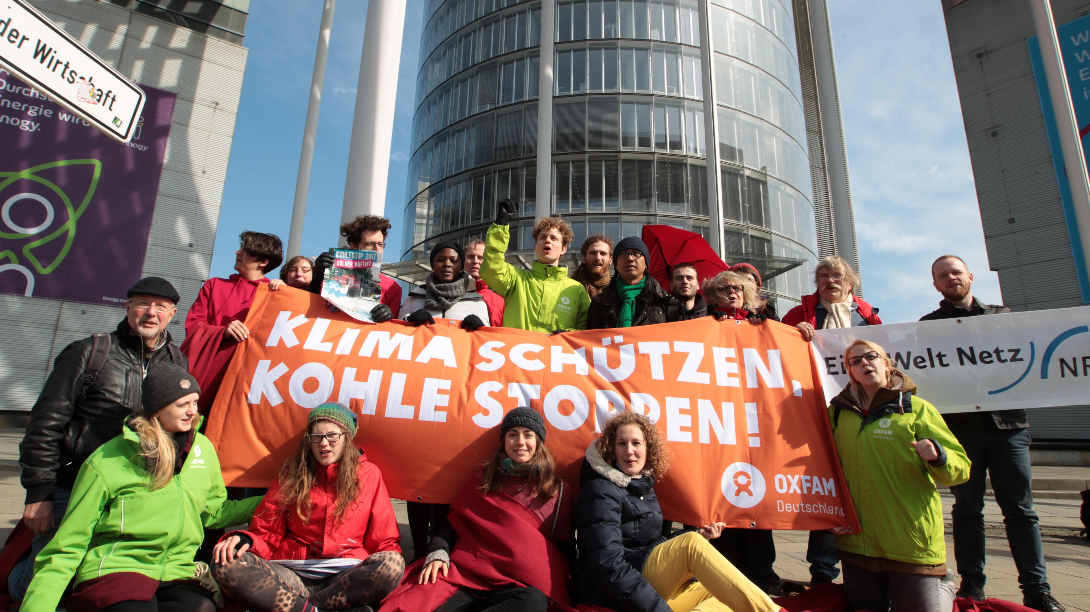 """Aktivist/innen protestieren mit einem Banner vor der RWE-Zentrale: """"Klima schützen, Kohle stoppen!"""""""