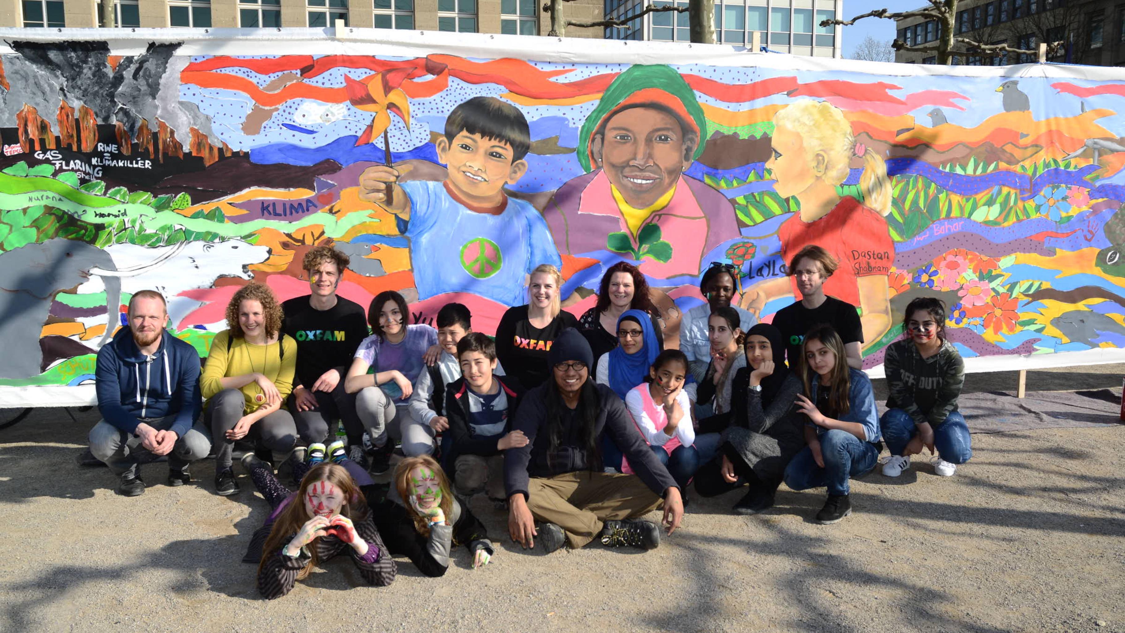 Künstler und Aktivist/innen vor dem fertigen Gemälde. Das Bild zeigt Kinder Asiens, Afrikas und Europas, die gemeinsam eine neue klimafreundliche Welt erschaffen.