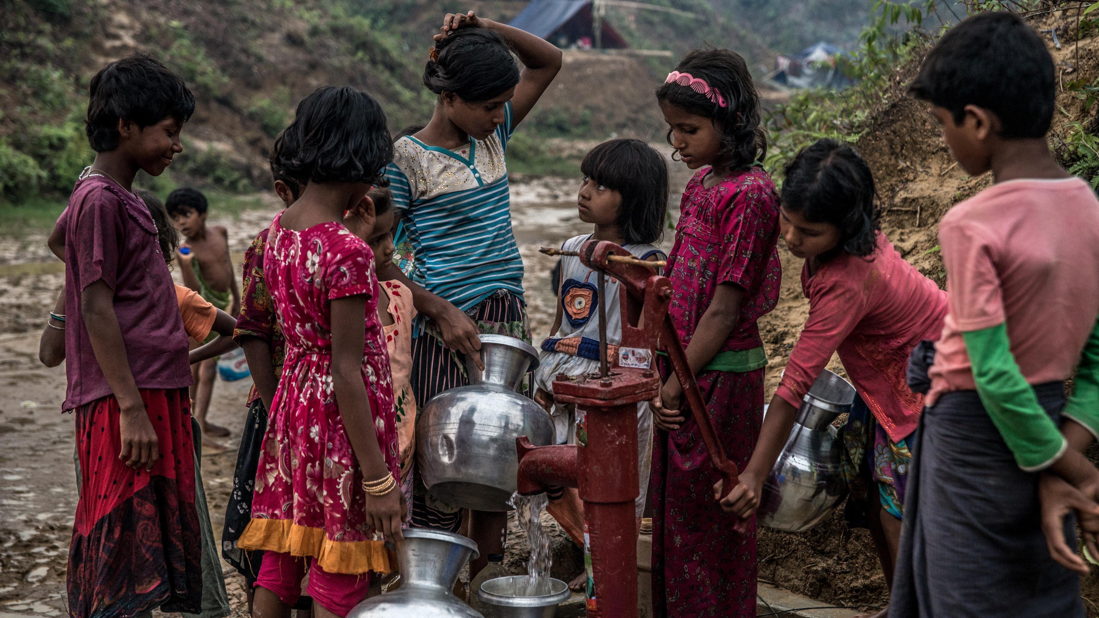 Eine Gruppe von Mädchen füllt an einer Pumpe Wasser in Behälter