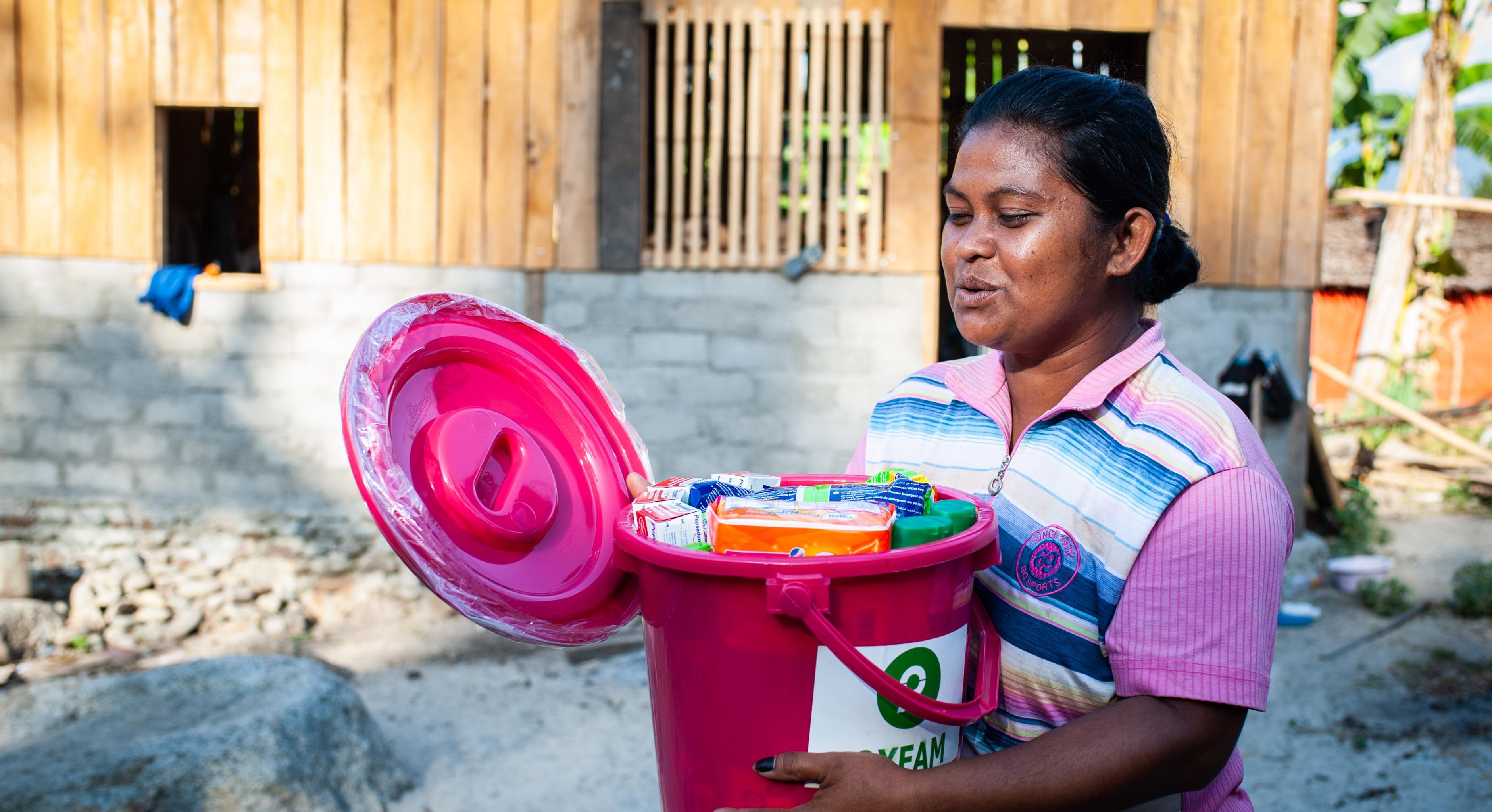 Eine Frau öffnet einen Oxfam-Plastikeimer, der mit Hygieneartikeln gefüllt ist.