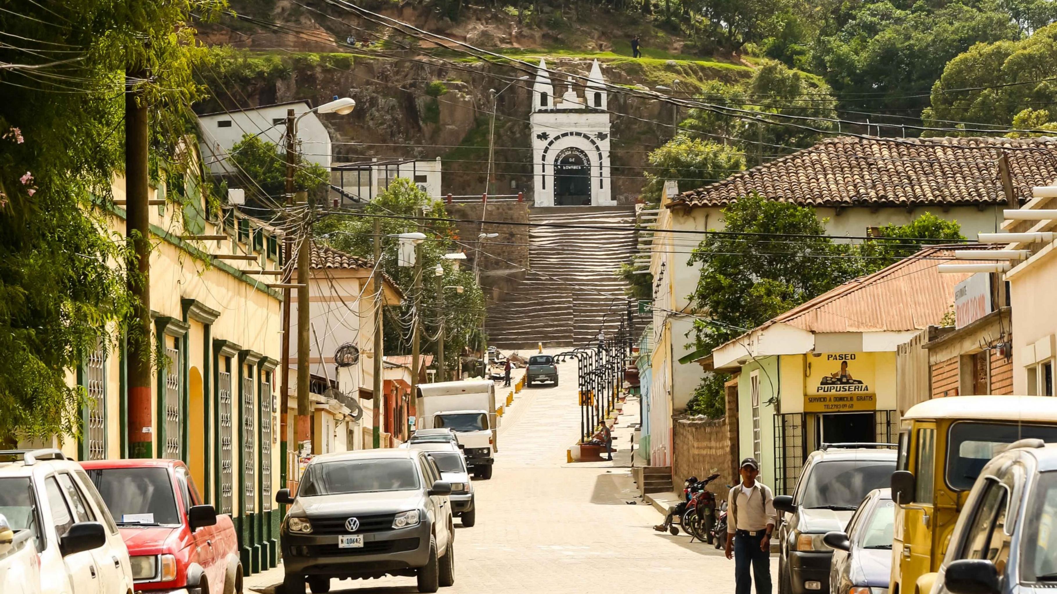Eine sonnige kleine Straße, gesäumt von Autos und niedrigen Häusern, führt bergauf. Am Ende der Straße führt eine Treppe zu einer Kapelle an einem bewaldeten Berg.