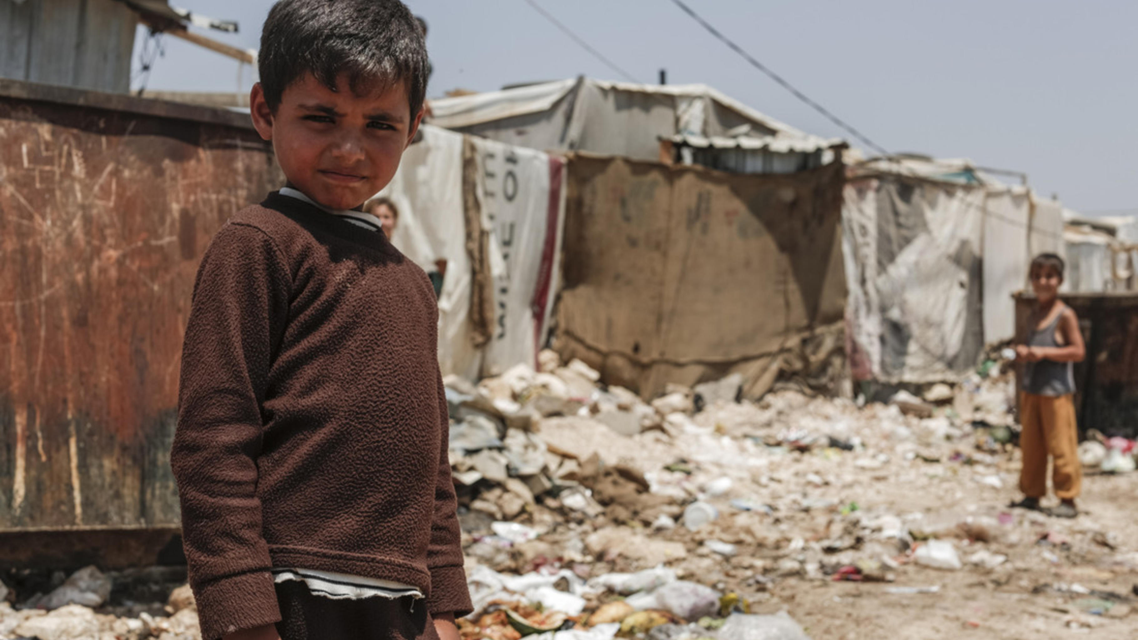 Ein Kind in einem Flüchtlingscamp blickt in die Kamera