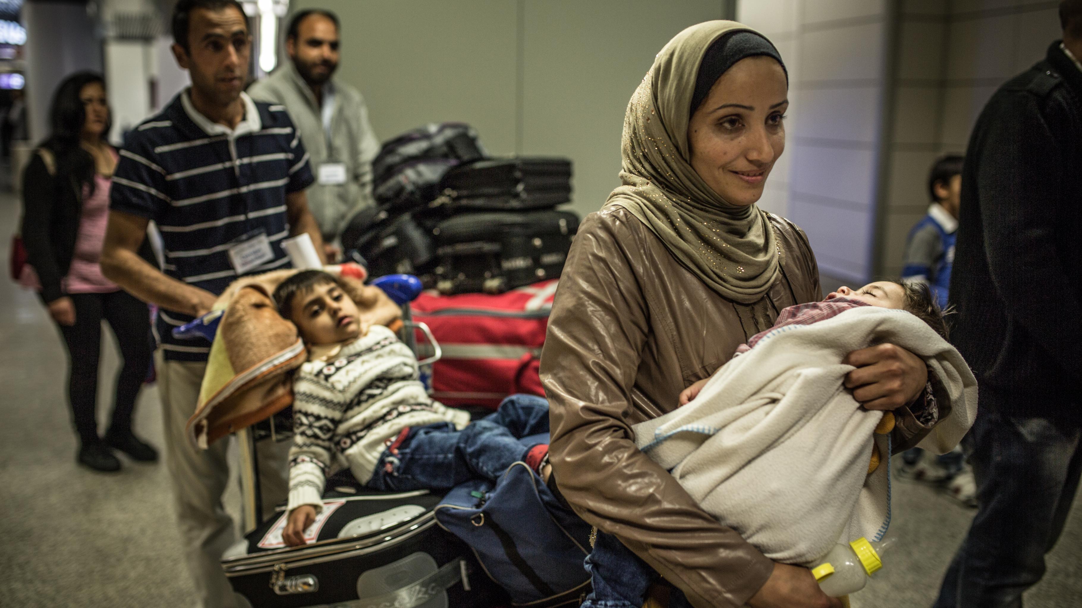 Eine Frau mit einem kleinen Kind auf dem Arm geht durch die Ankunftshalle eines Flughafens; hinter ihr schiebt ein Mann einen Kofferkuli mit Gepäck, auf dem ein müder Junge sitzt.