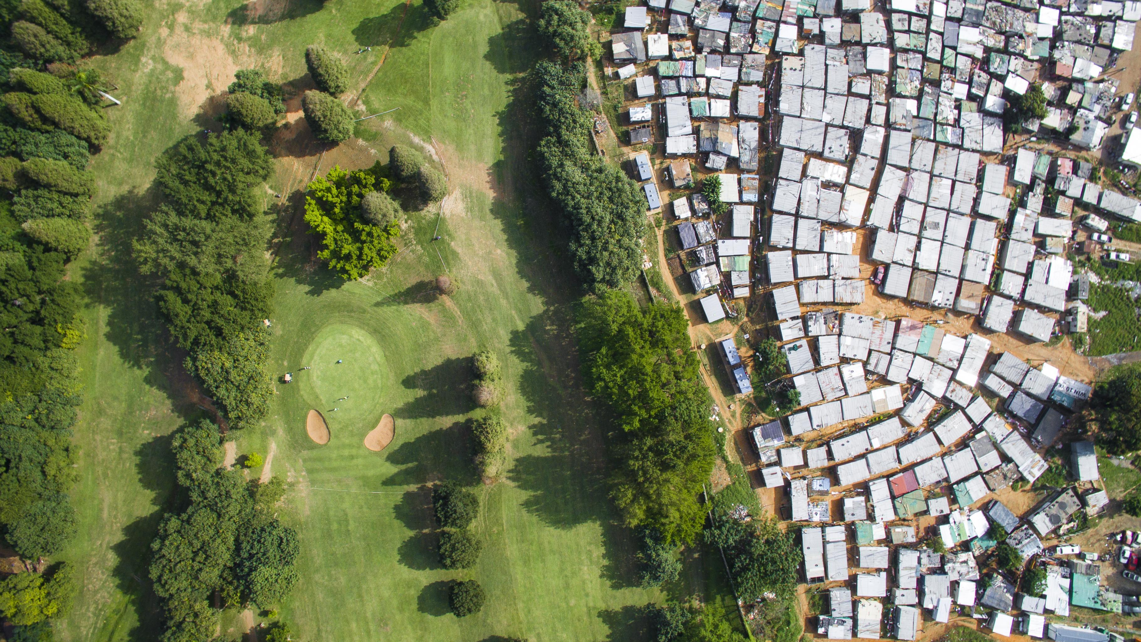Luftaufnahme: Ein Golfplatz und ein Slum