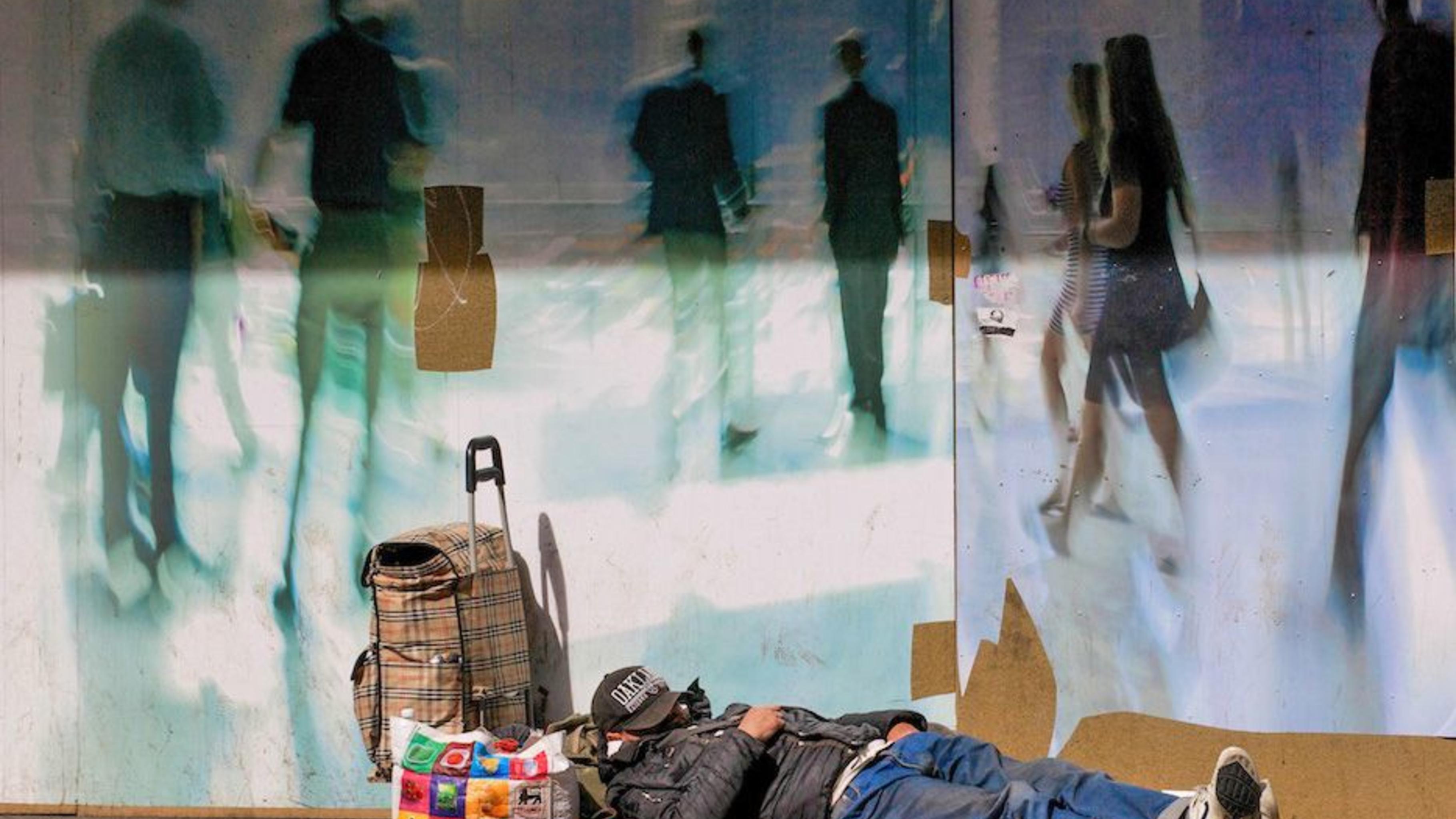 Ein Obdachloser liegt in einem Börsenviertel am Straßenrand.