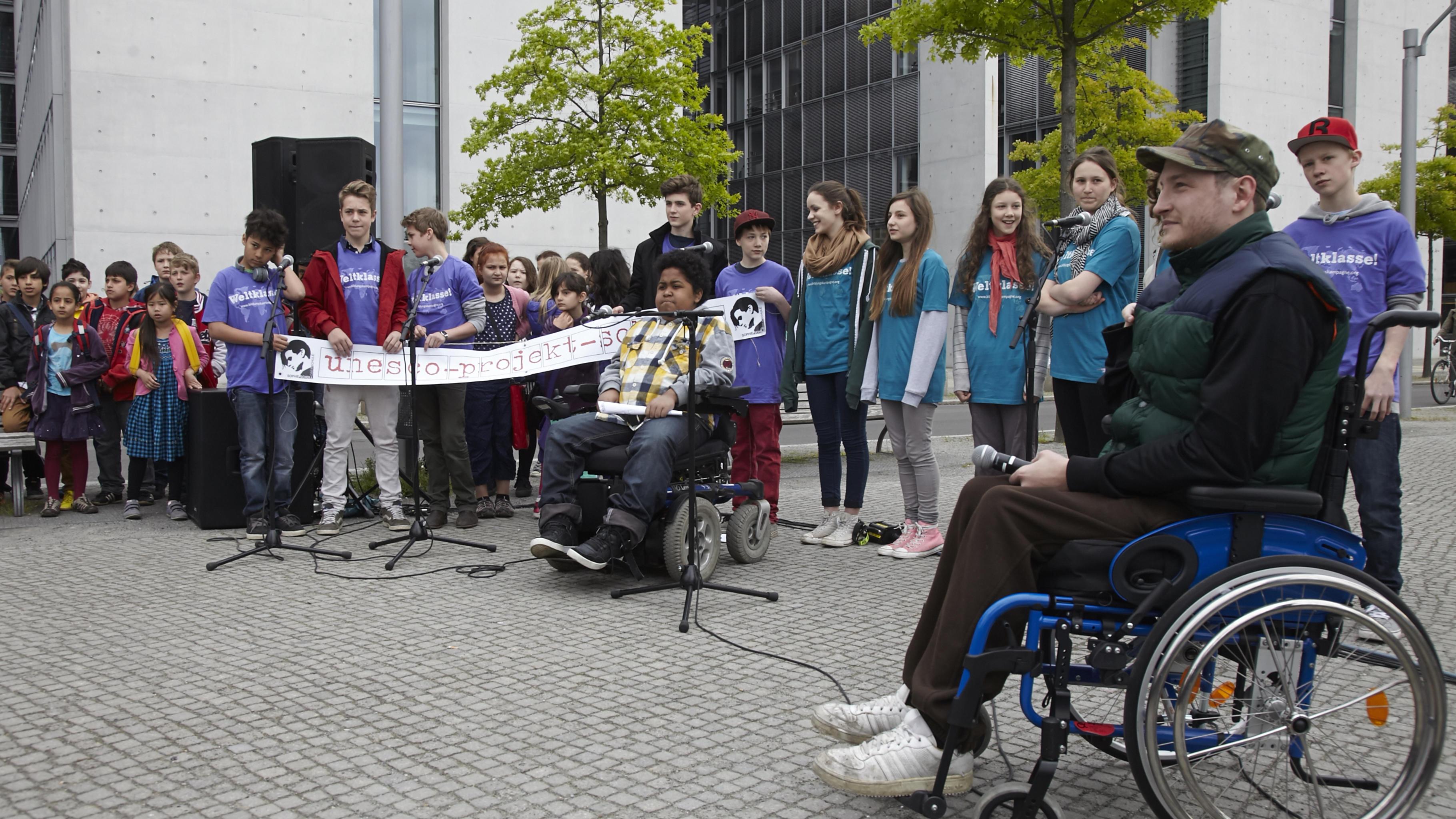 Schüler/-innen der Sophie-Scholl-Schule und der Rollstuhl-Rapper Graf Fidi rappe