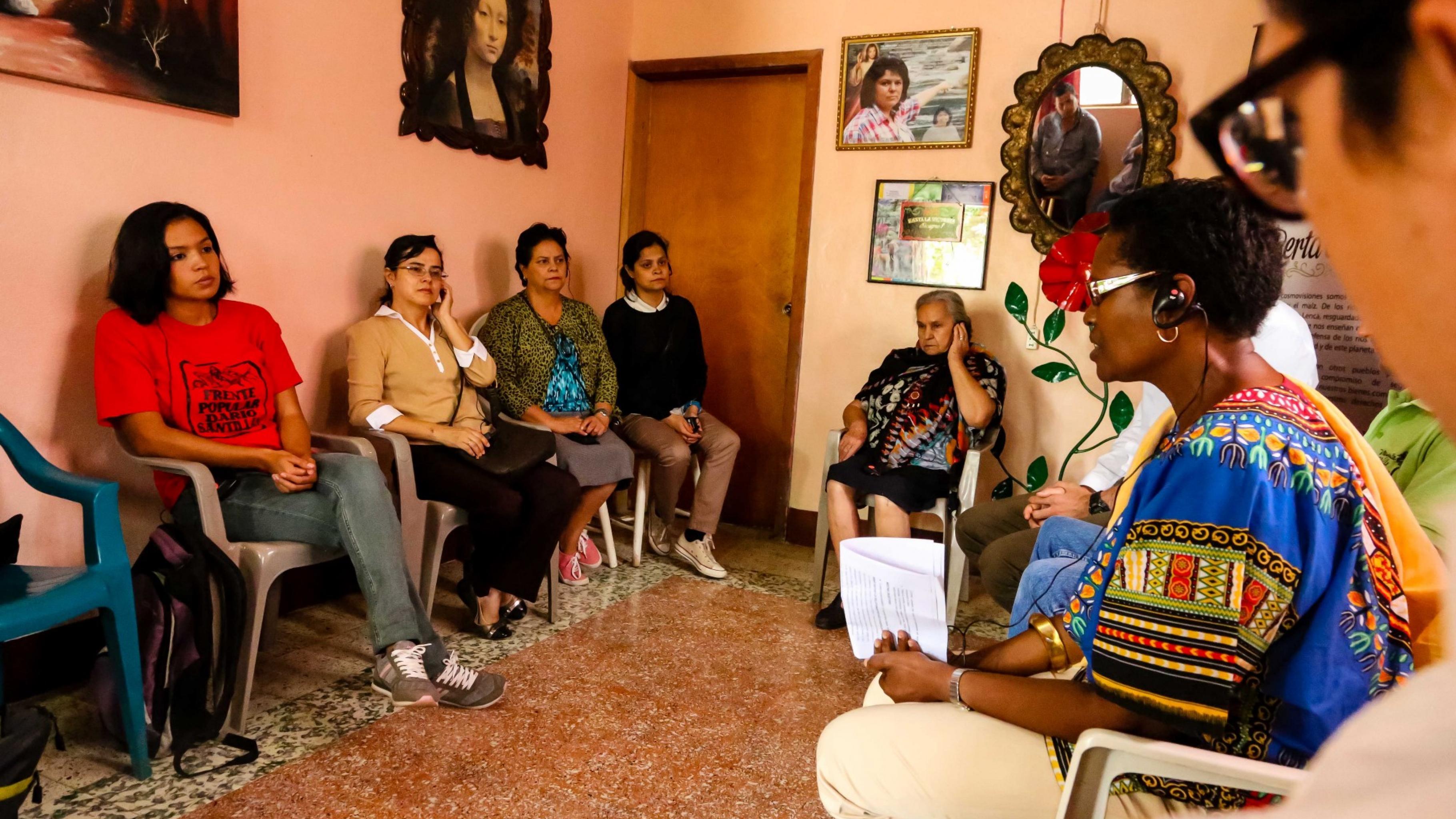 In einem Zimmer sitzen Frauen und Männer auf Plastikstühlen im Kreis und sprechen miteinander. An den Wänden hängen Bilder, unter anderem von Berta Cáceres.