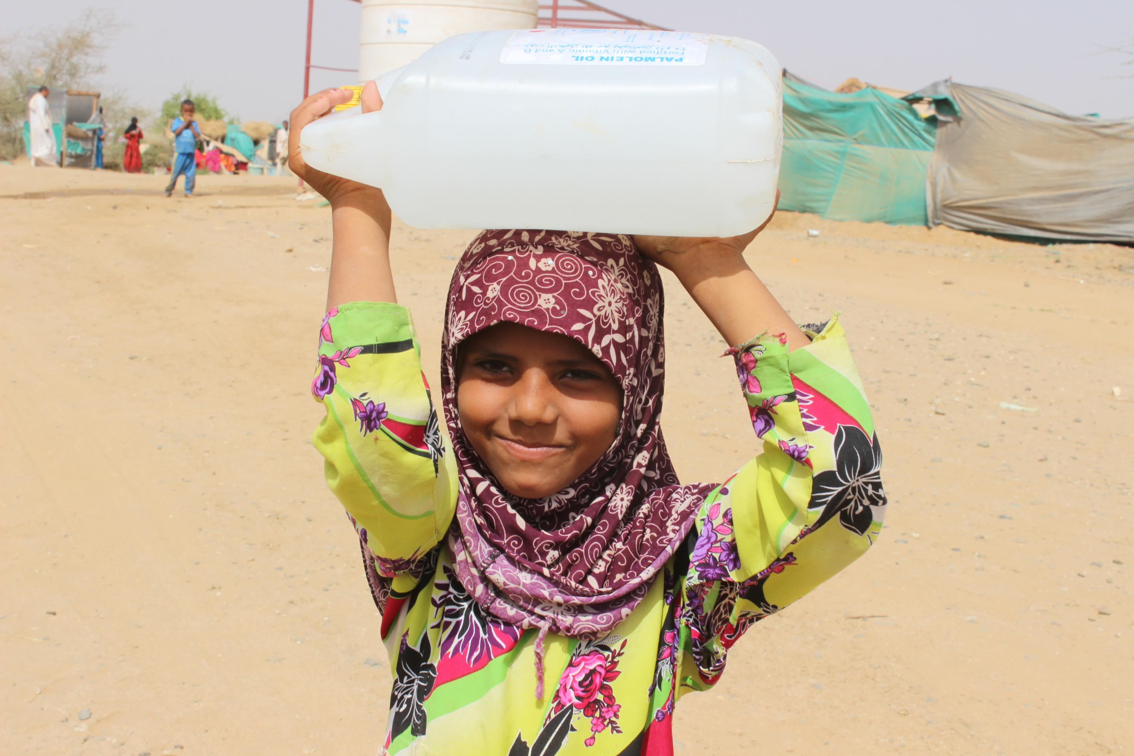 Mädchen aus dem Jemen trägt einen Kanister Wasser