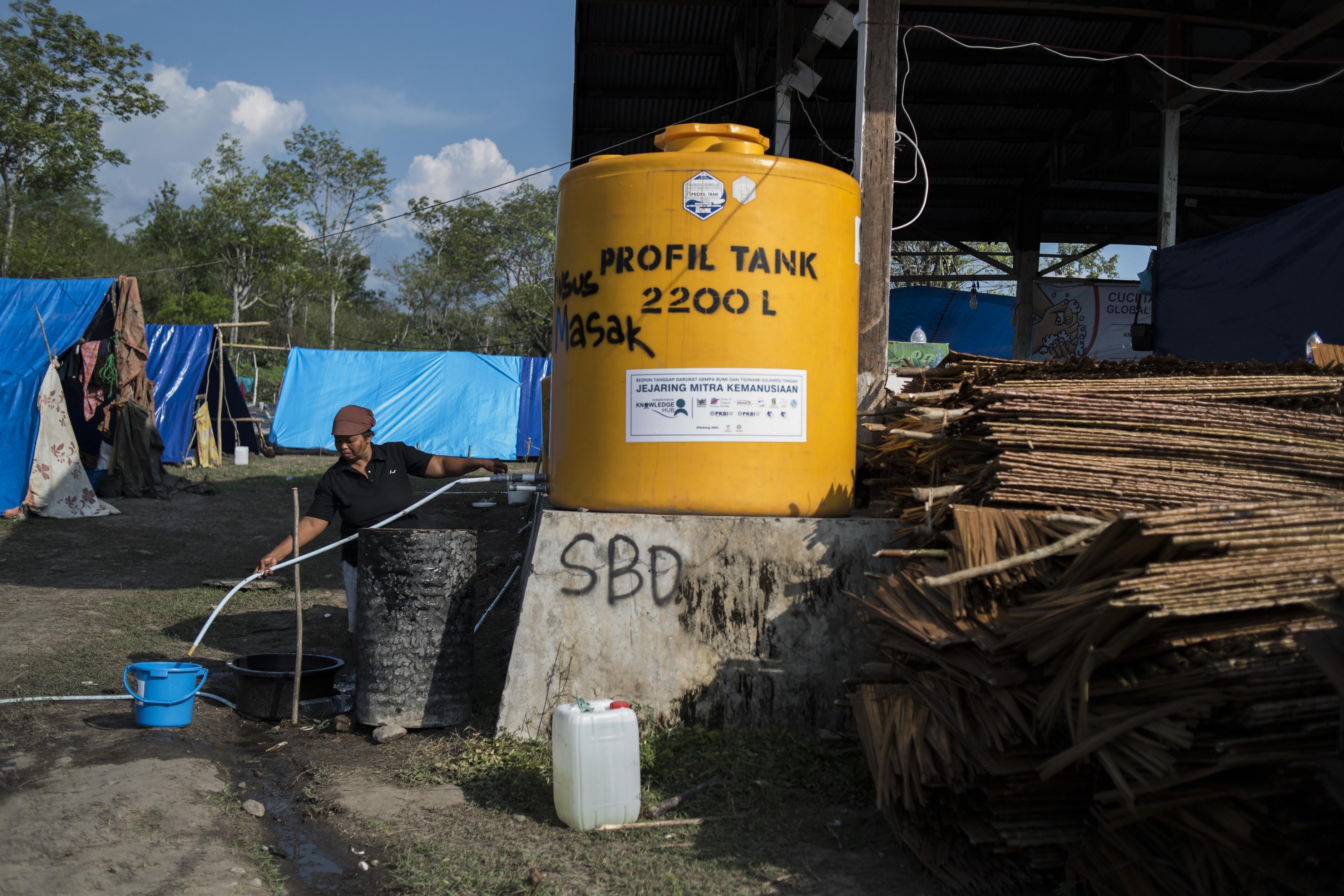 Ein Mann füllt seinen Eimer mit sauberem Wasser aus einem Kanister