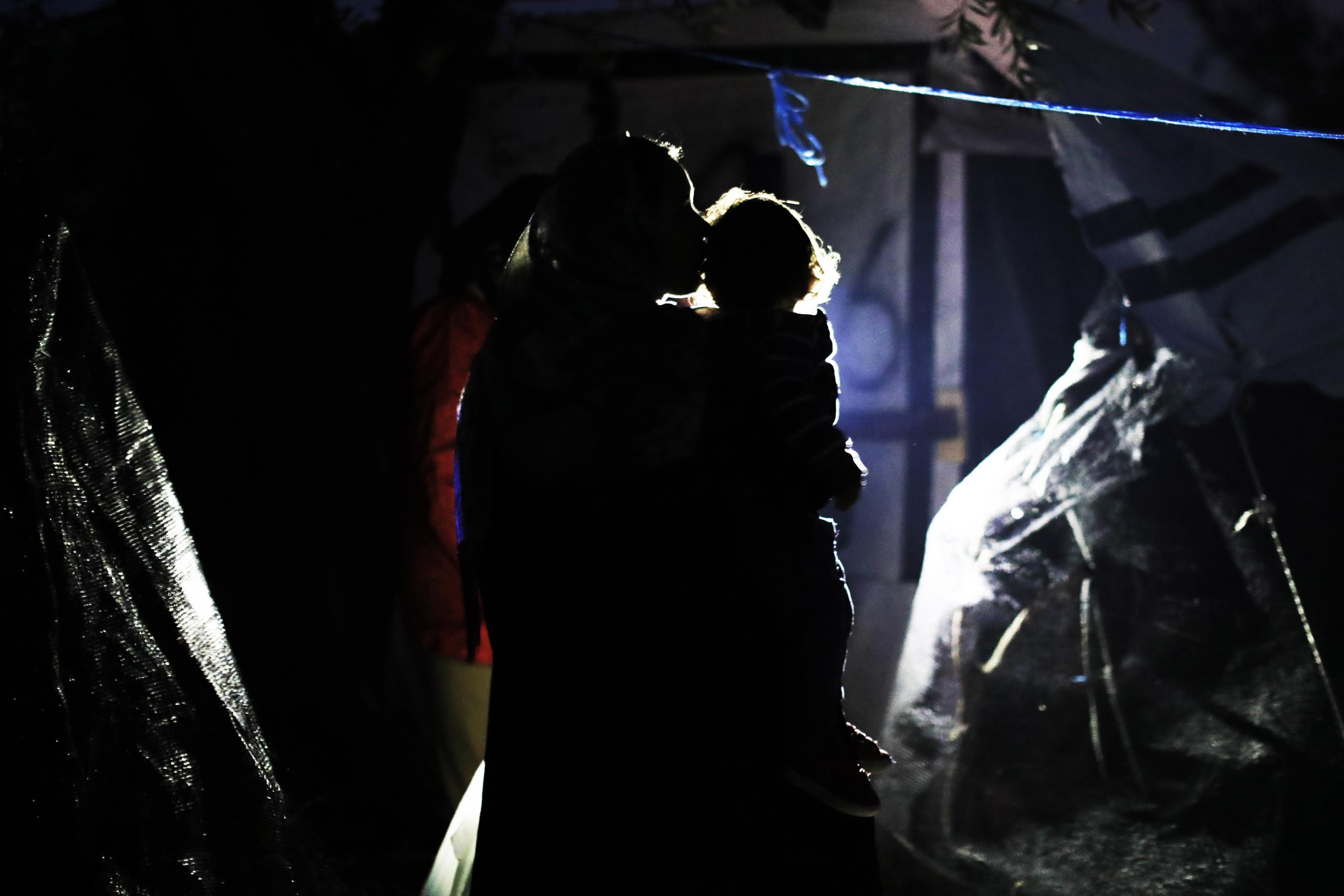 Eine Frau trägt ihr Kind in einem Flüchtlingscamp