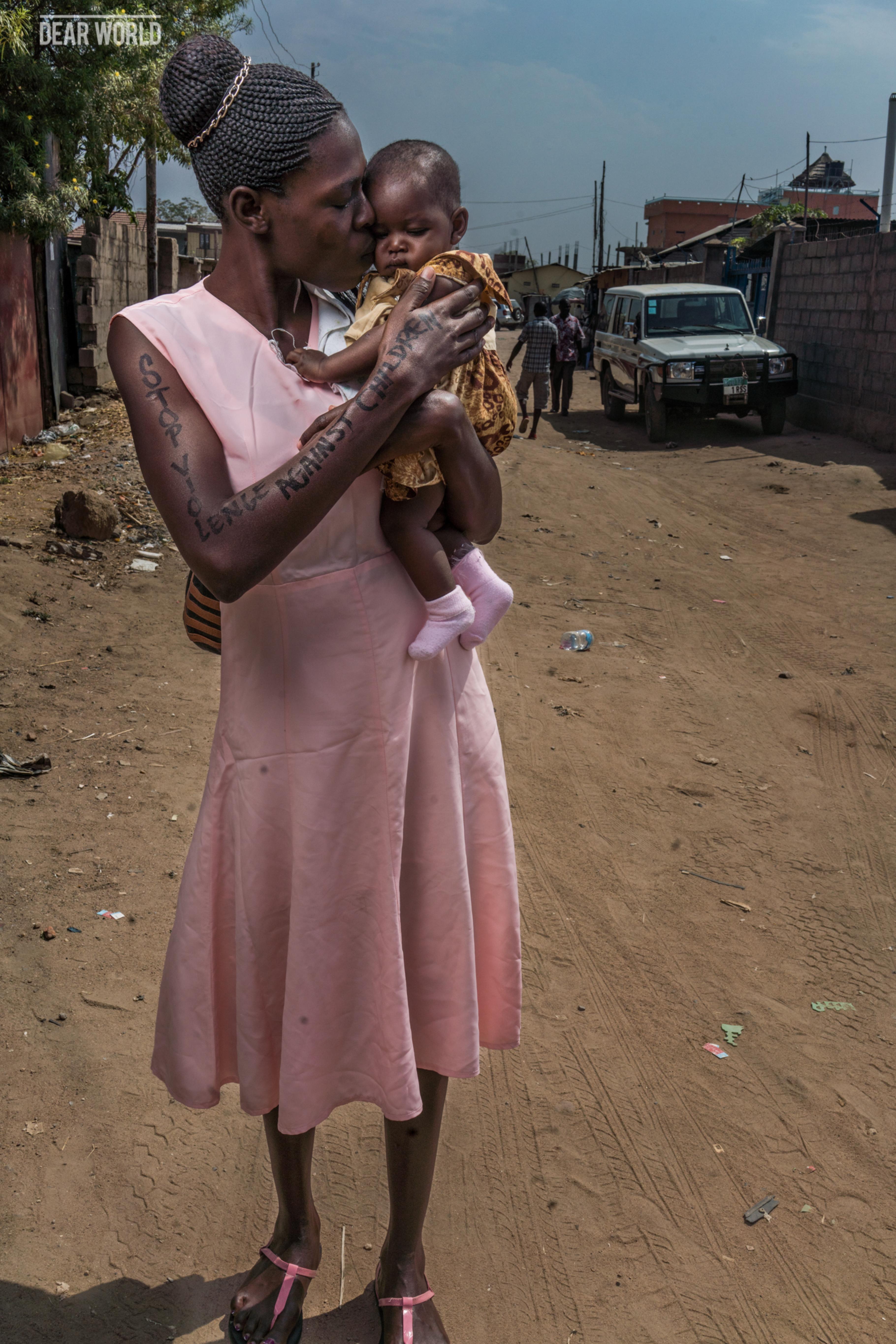 Eine Frau hält ein Baby auf dem Arm und küsst es auf die Wange. Auf ihrem Arm ist zu lesen Stop violence against children.