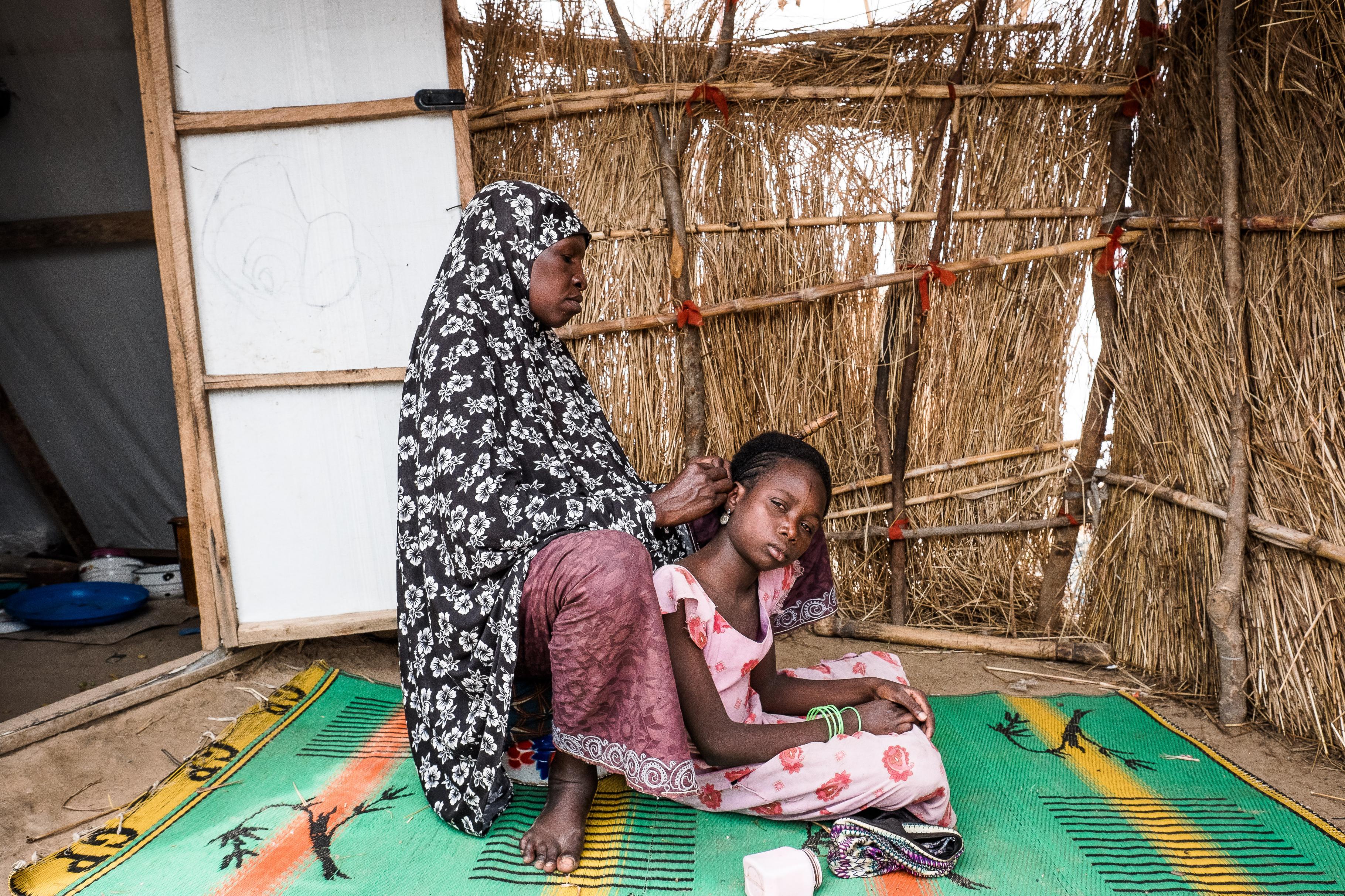 Hassana flechtet die Haare ihrer Tochter in einem Camp in Damboa in Nigeria