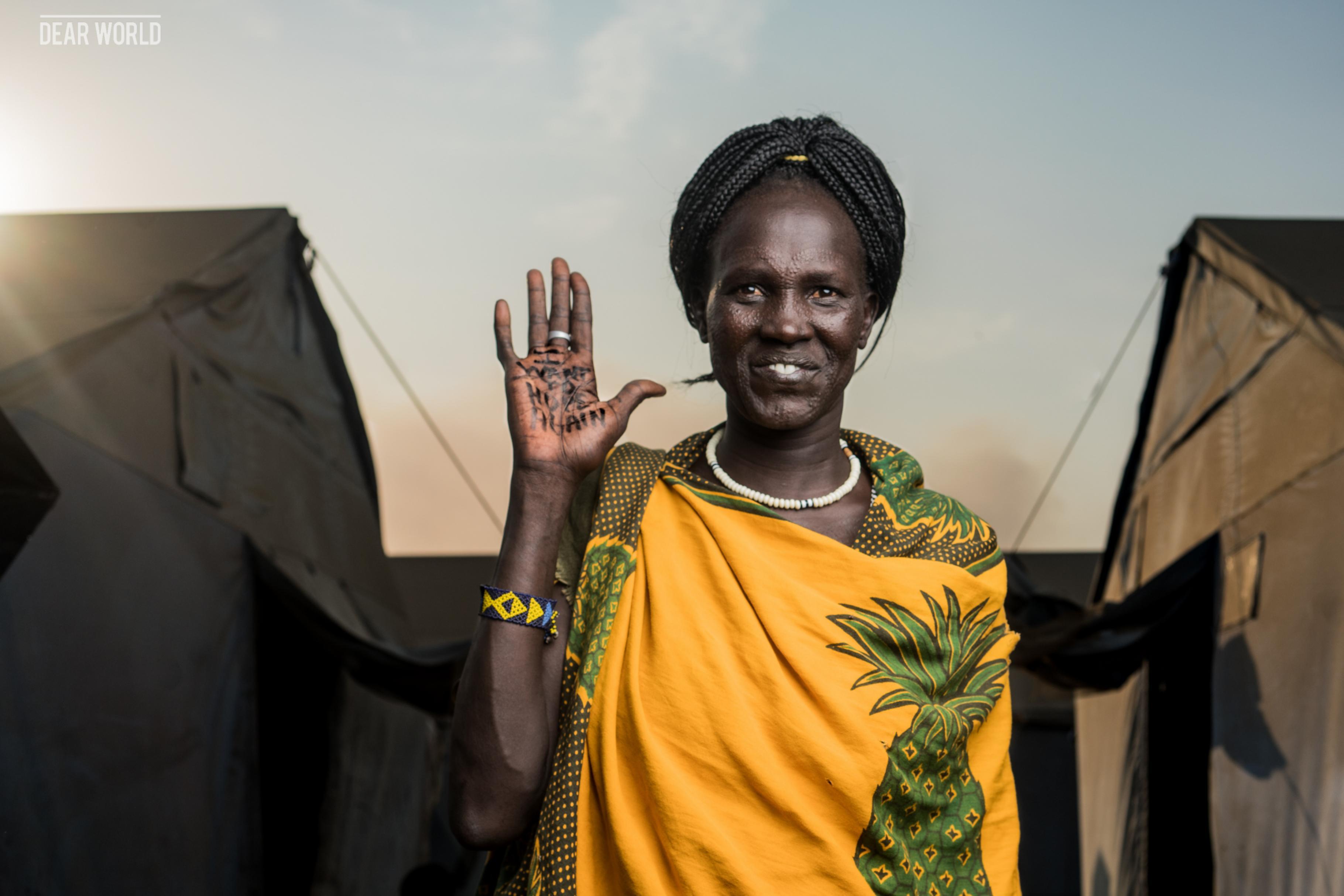 EIne Frau vor dem Hintergrund von zwei Zelten hält ihre Handfläche in die Kamera. Auf der Handfläche ist zu lesen I want to hope again.