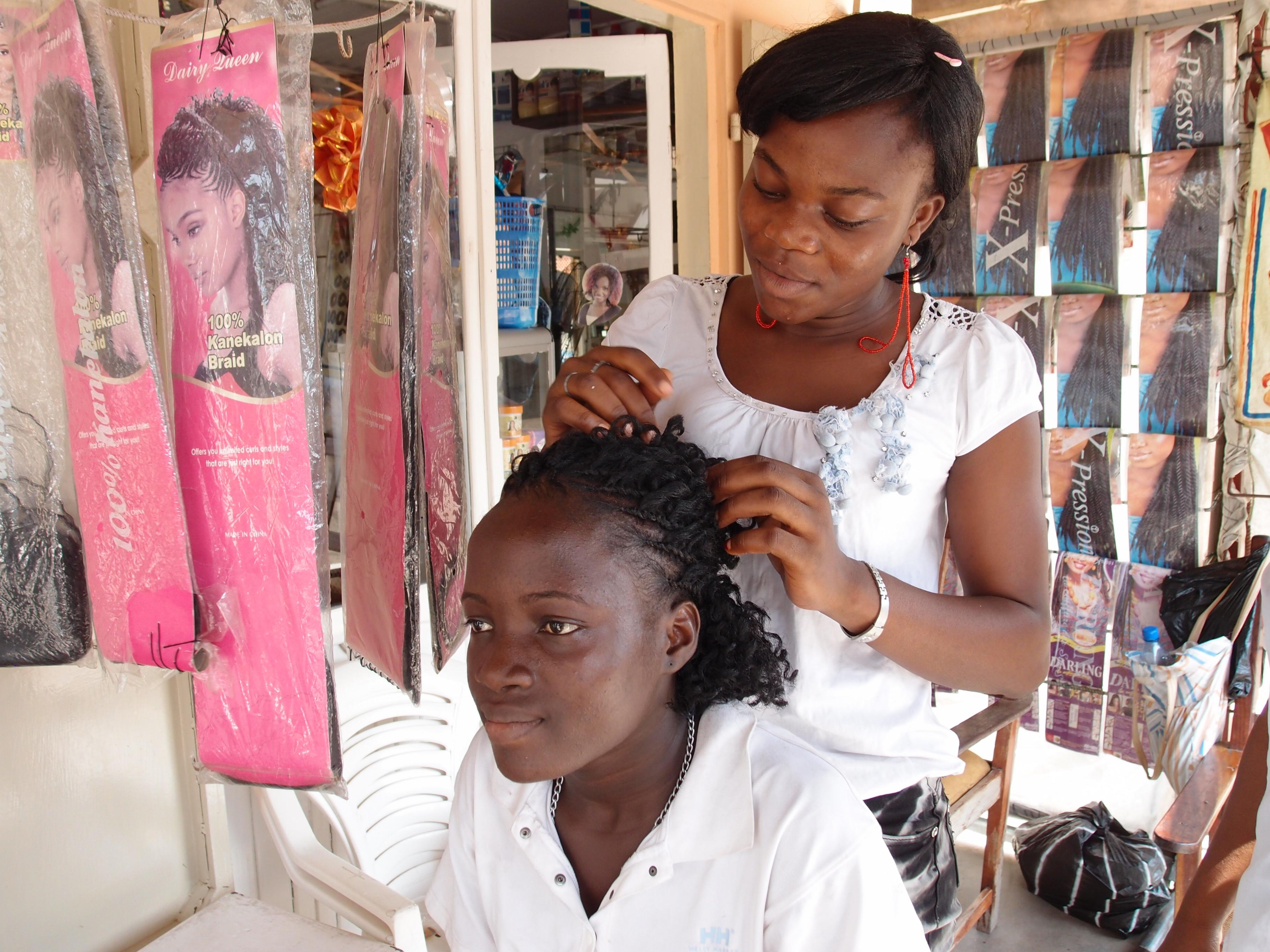 Frau beim Haareschneiden: Berufsausbildung zum Friseur in Benin