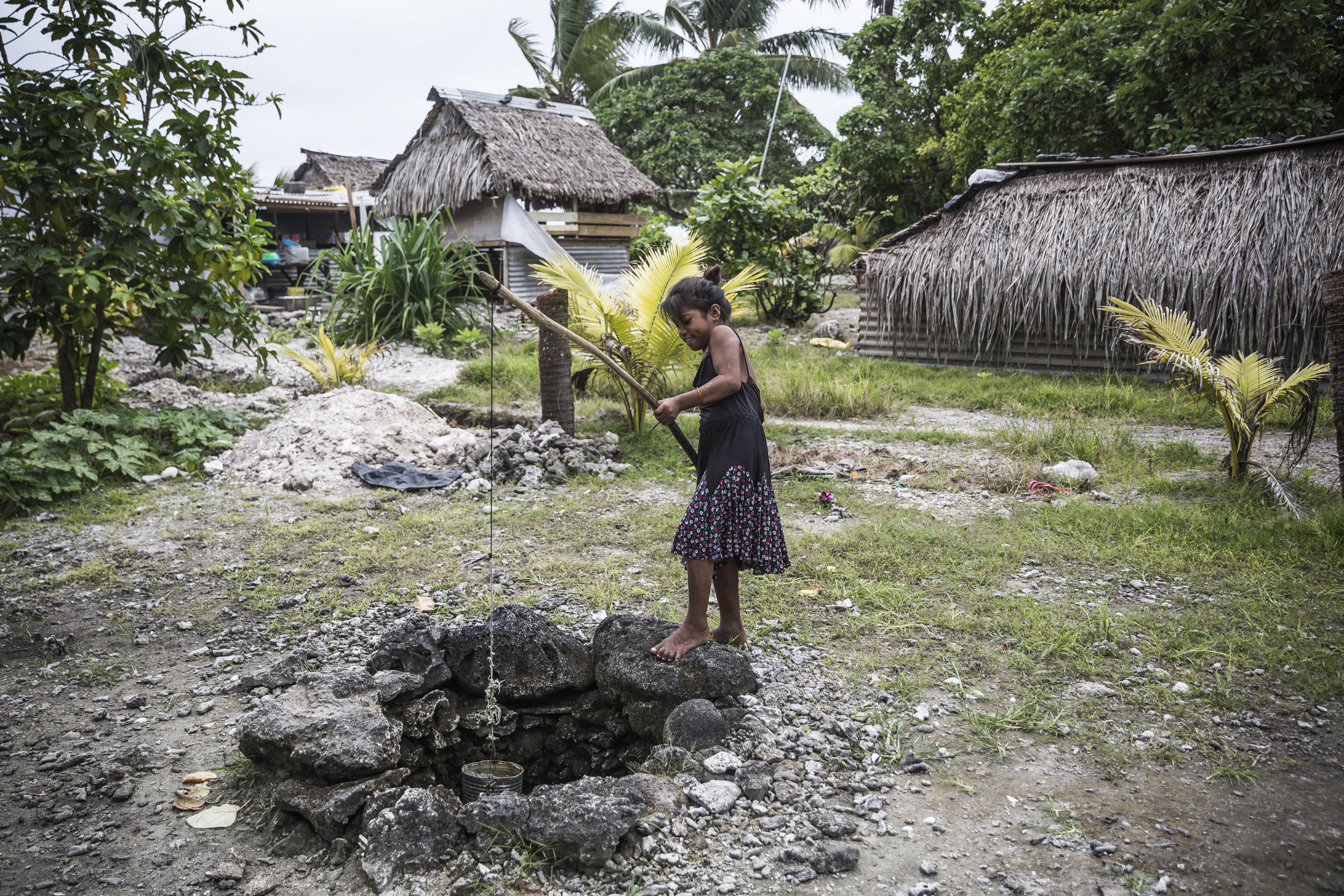 Ein Mädchen holt Wasser aus einem einfachen Brunnen.