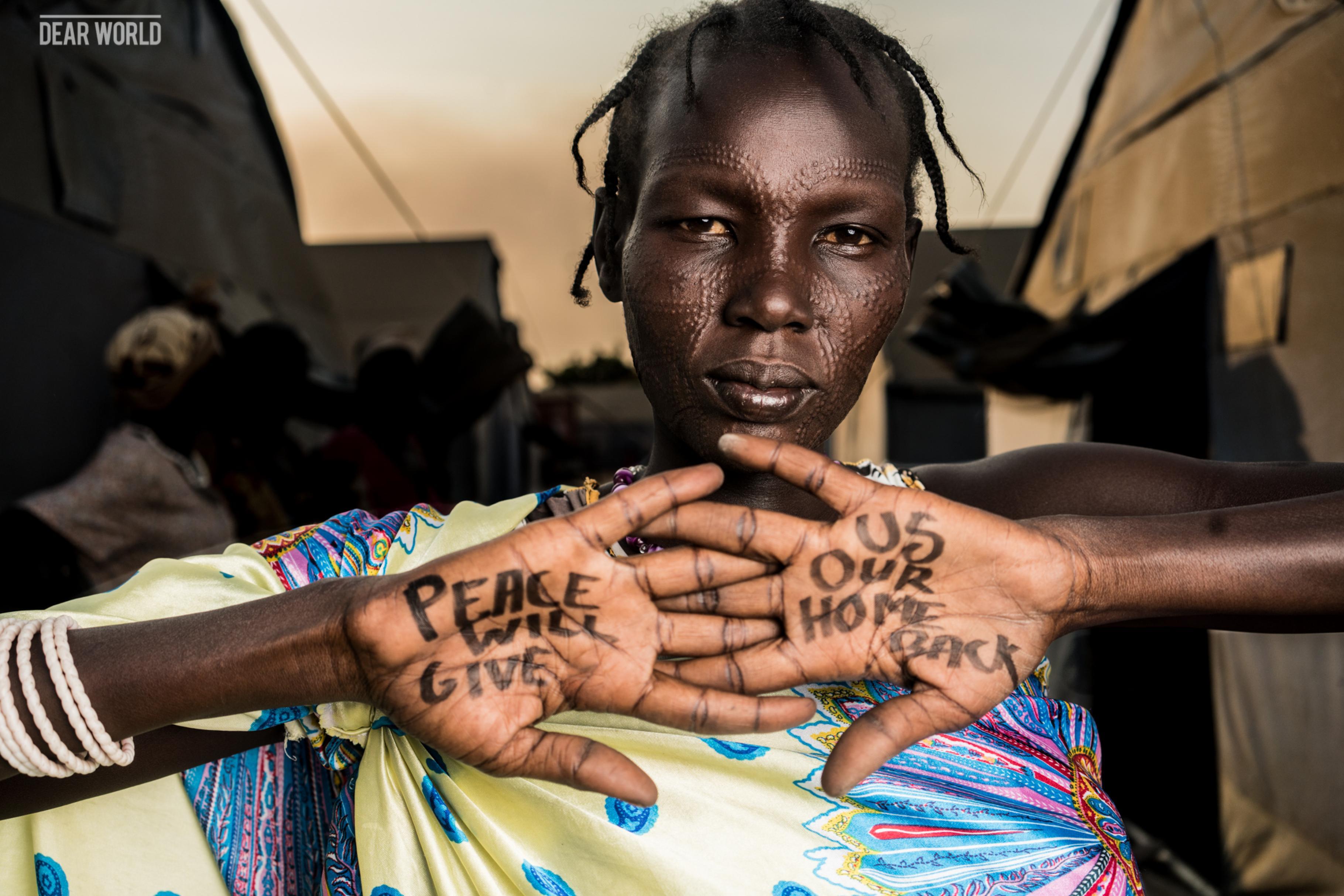 Eine Frau hält ihre Handinnenflächen in die Kamera. Auf den Handflächen ist zu lesen Peace will give us our home back (Mary Moses)