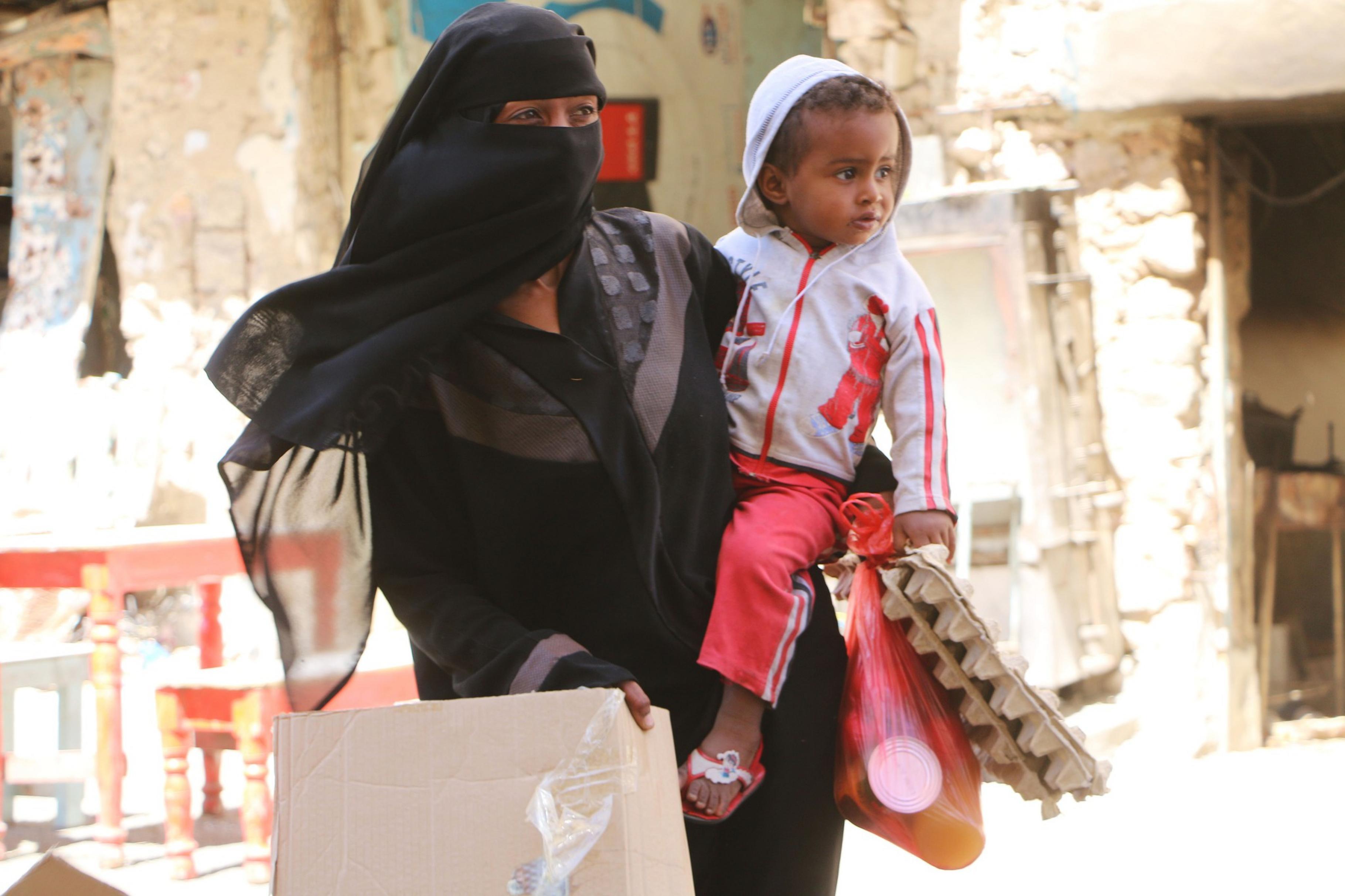 Eine Frau in Jemen trägt ihr Kind auf dem Arm.