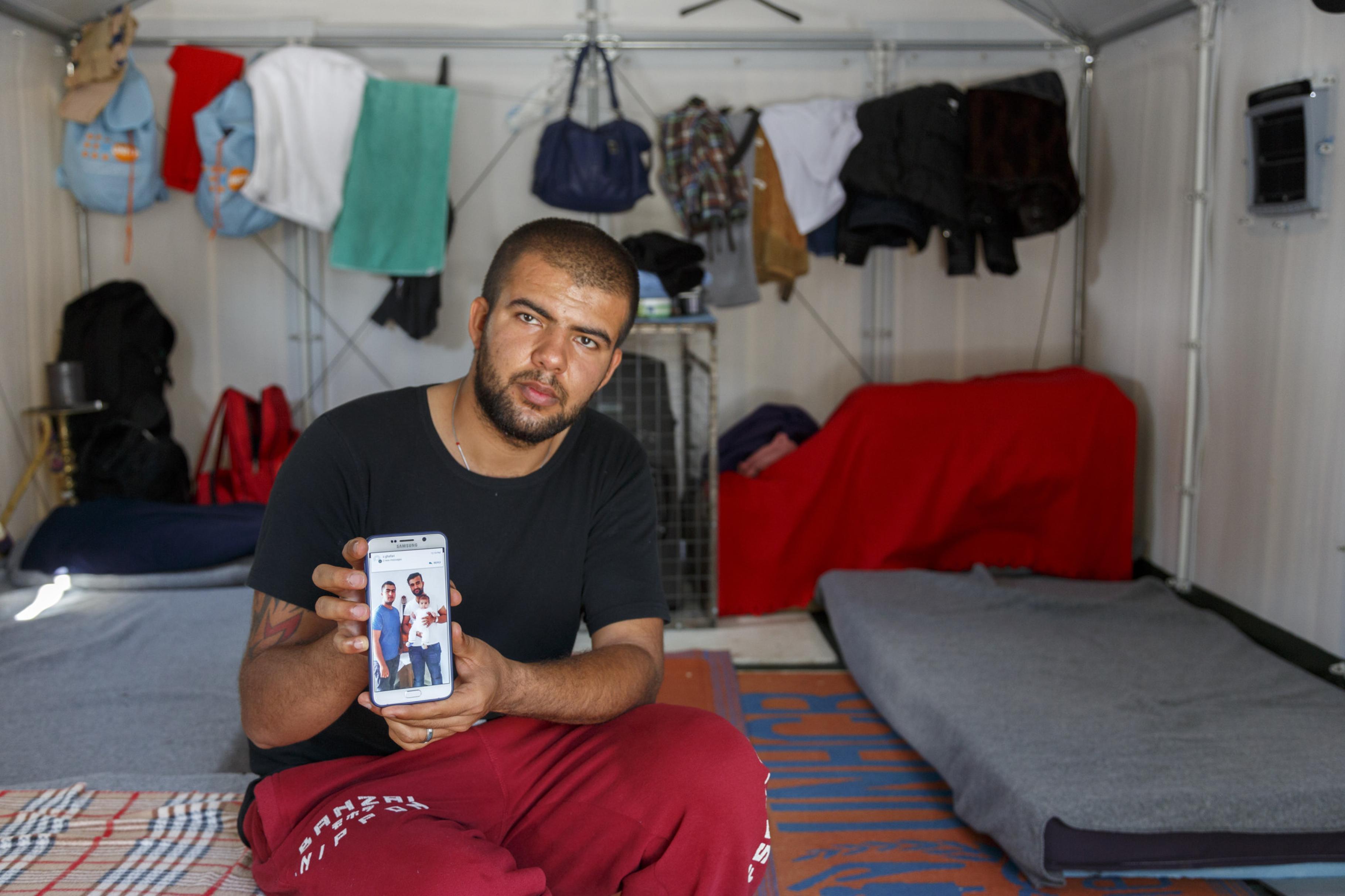 Faramaz zeigt sein Handydisplay, auf dem drei Verwandte von ihm zu sehen sind