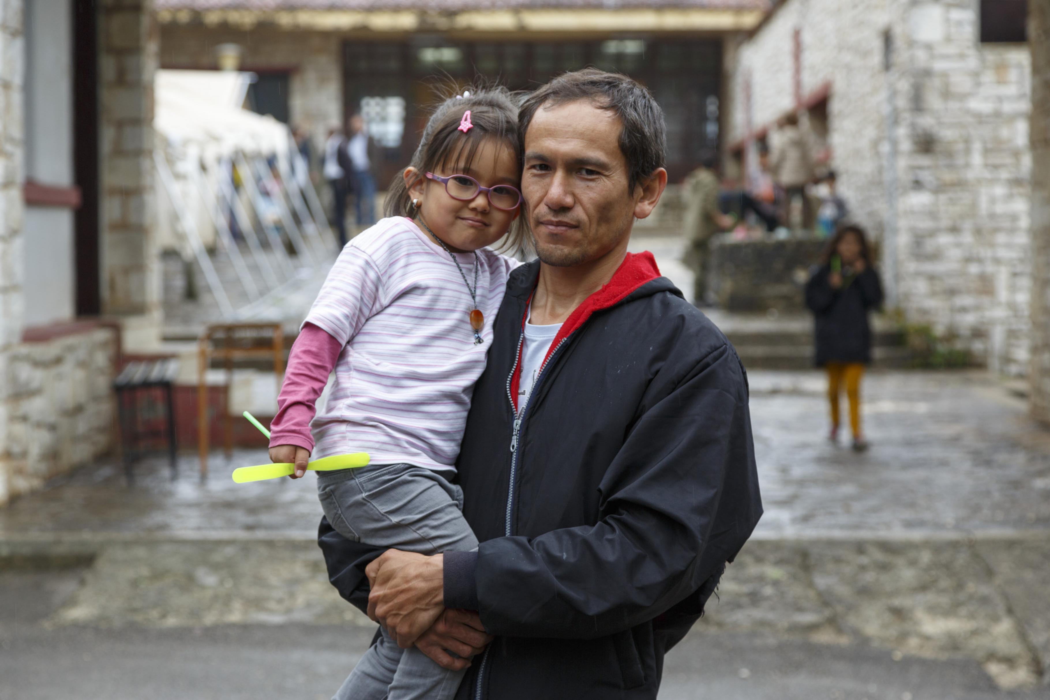 Ein Vater hält seine Tochter auf dem Arm, im Hintergrund ist ein größeres Steingebäude zu sehen