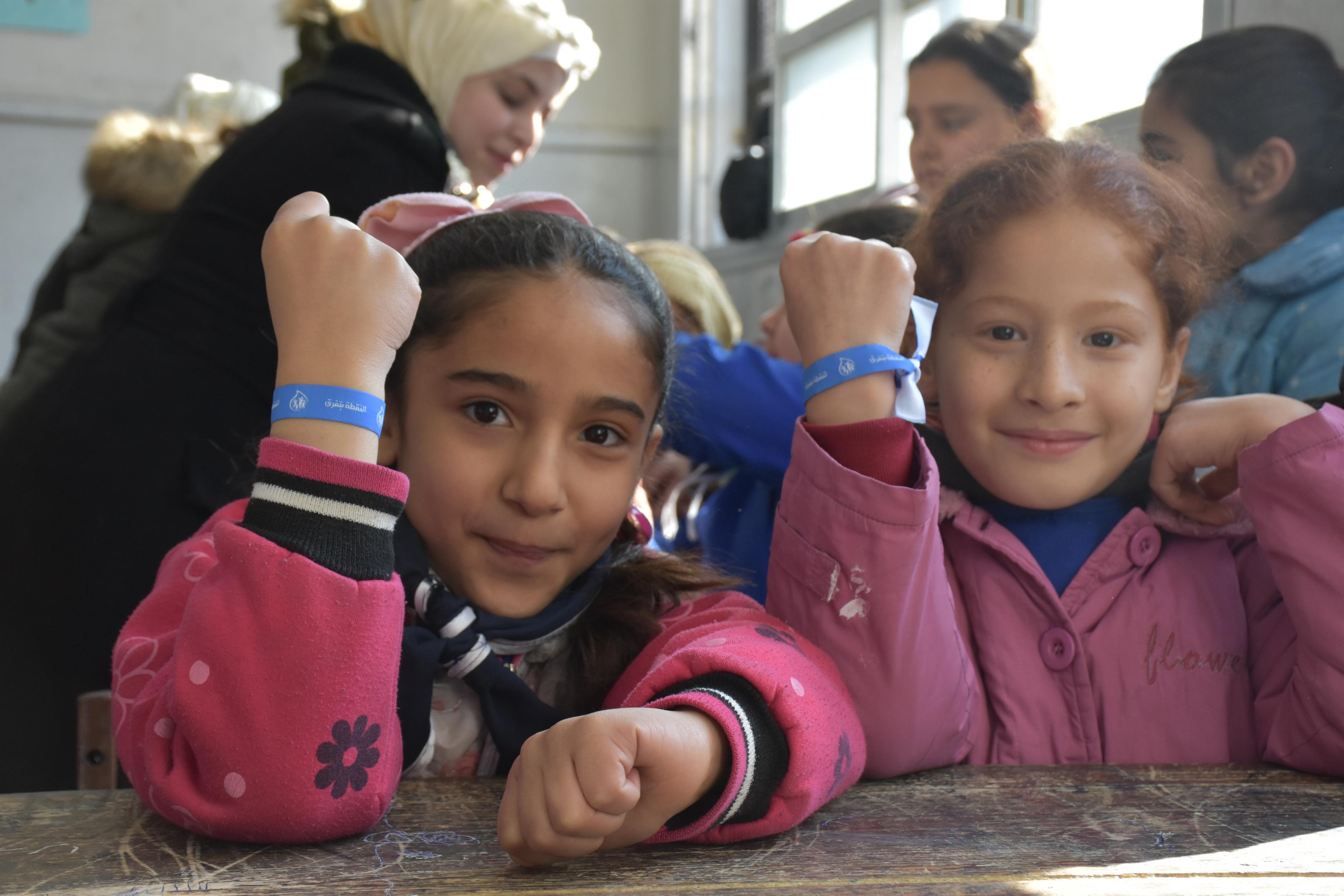 Zwei Schülerinnen zeigen ihre Armbänder