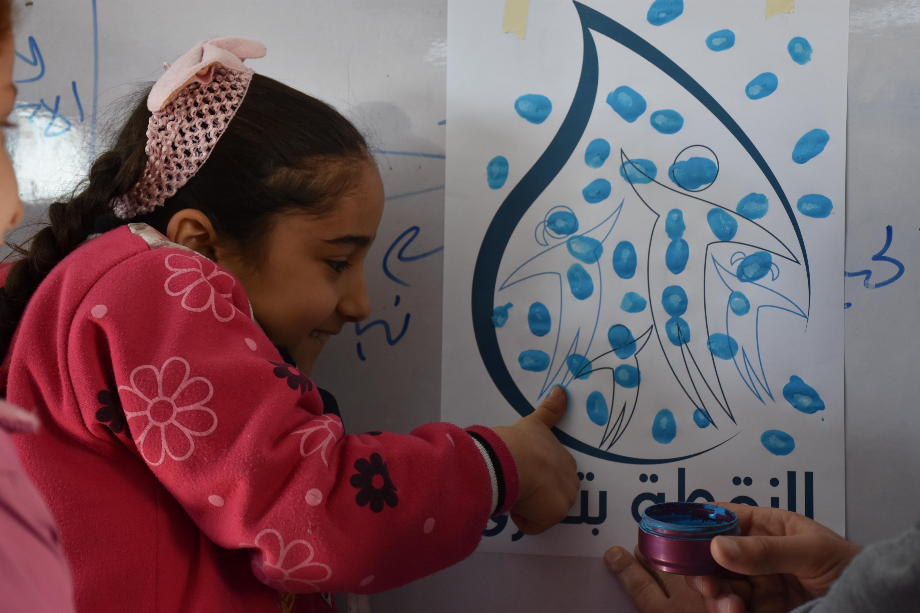 Eine Schülerin macht einen Fingerabdruck auf ein Poster
