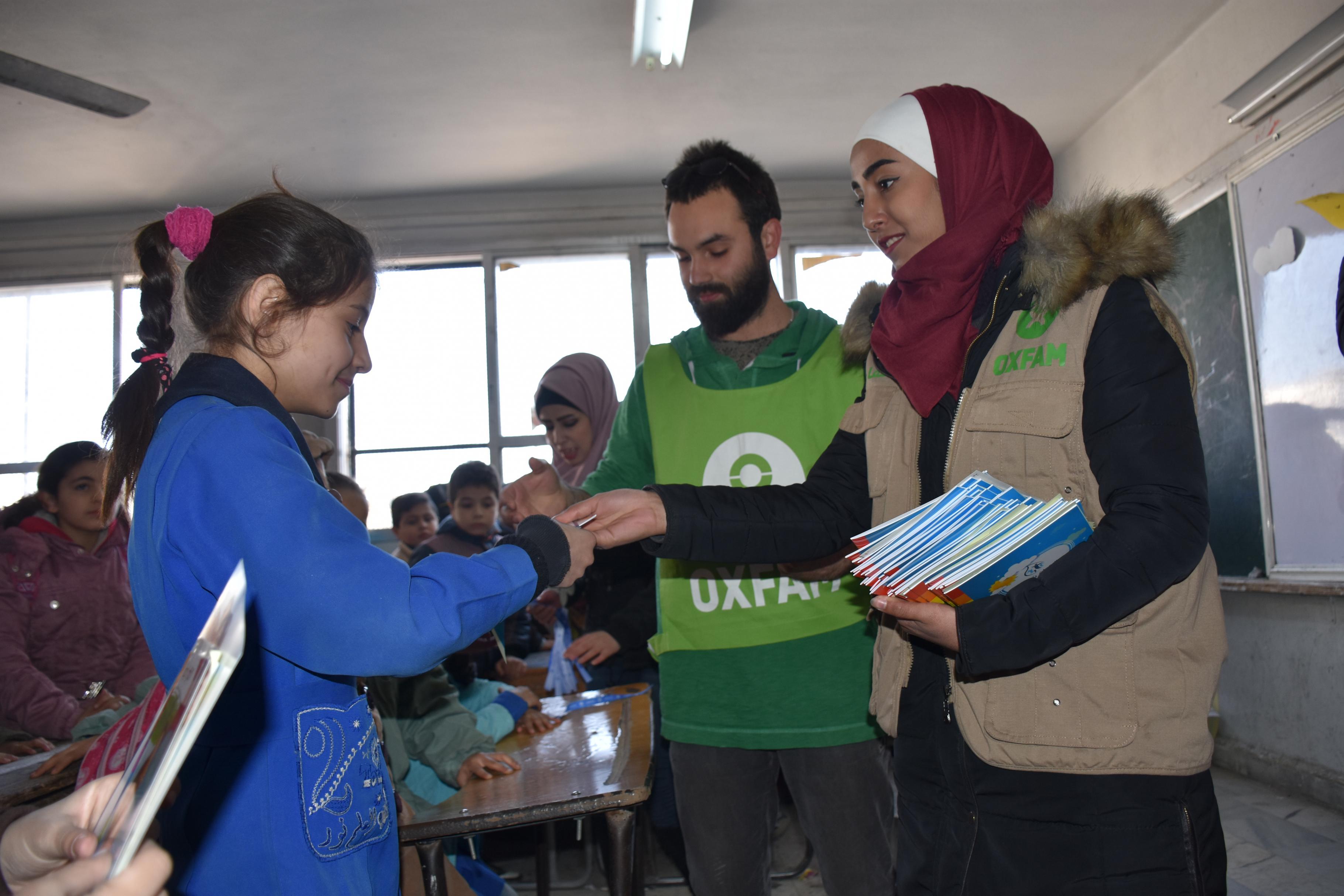 Freiwillige verteilen Malbücher an Schüler/innen