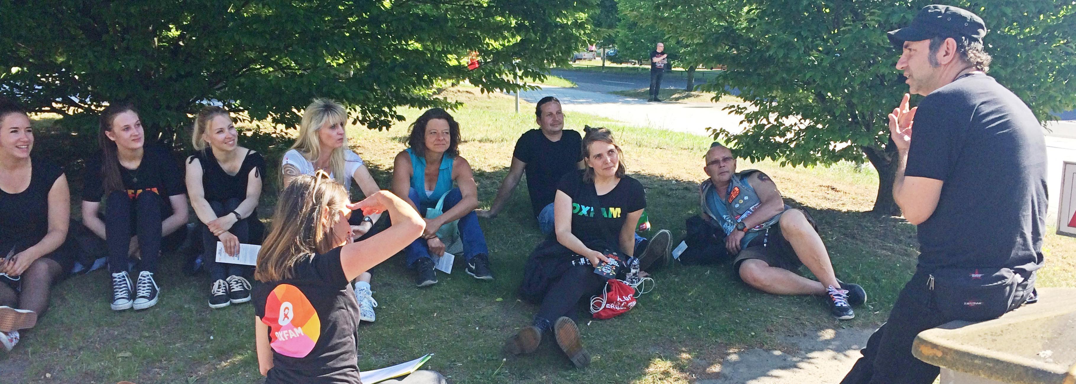 Eine Gruppe Konzertaktivist/innen sitzt im Schatten von Bäumen, während Ole Plogstedt erzählt